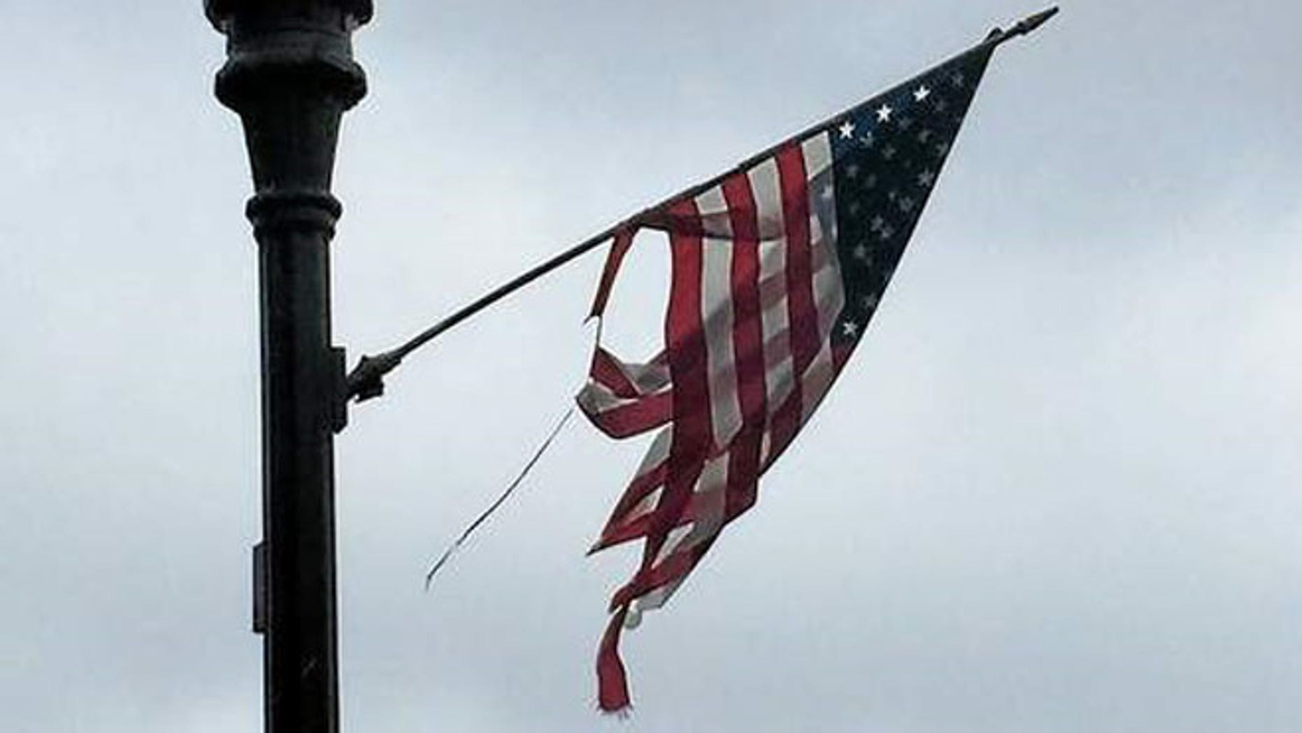 Most of the two dozen flags hanging from the black light posts that line Main Street in Derby, Conn. are either tattered and torn, have broken sticks that have been pieced together with duct tape or are laying on the ground. (New Haven Register)