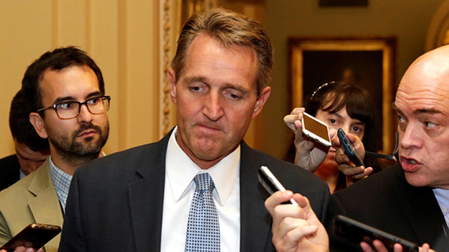 Senator Jeff Flake (R-AZ) talks to reporters as he arrives for a Senate health care vote on Capitol Hill in Washington, U.S., July 27, 2017. REUTERS/Yuri Gripas - RTX3D760