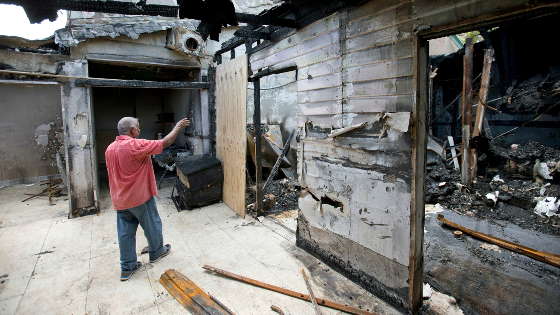 Sept. 15, 2016:  Farhad Khan, who has attended the Islamic Center of Fort Pierce for more than seven years, shows members of the media its charred remains, in Fort Pierce, Fla.