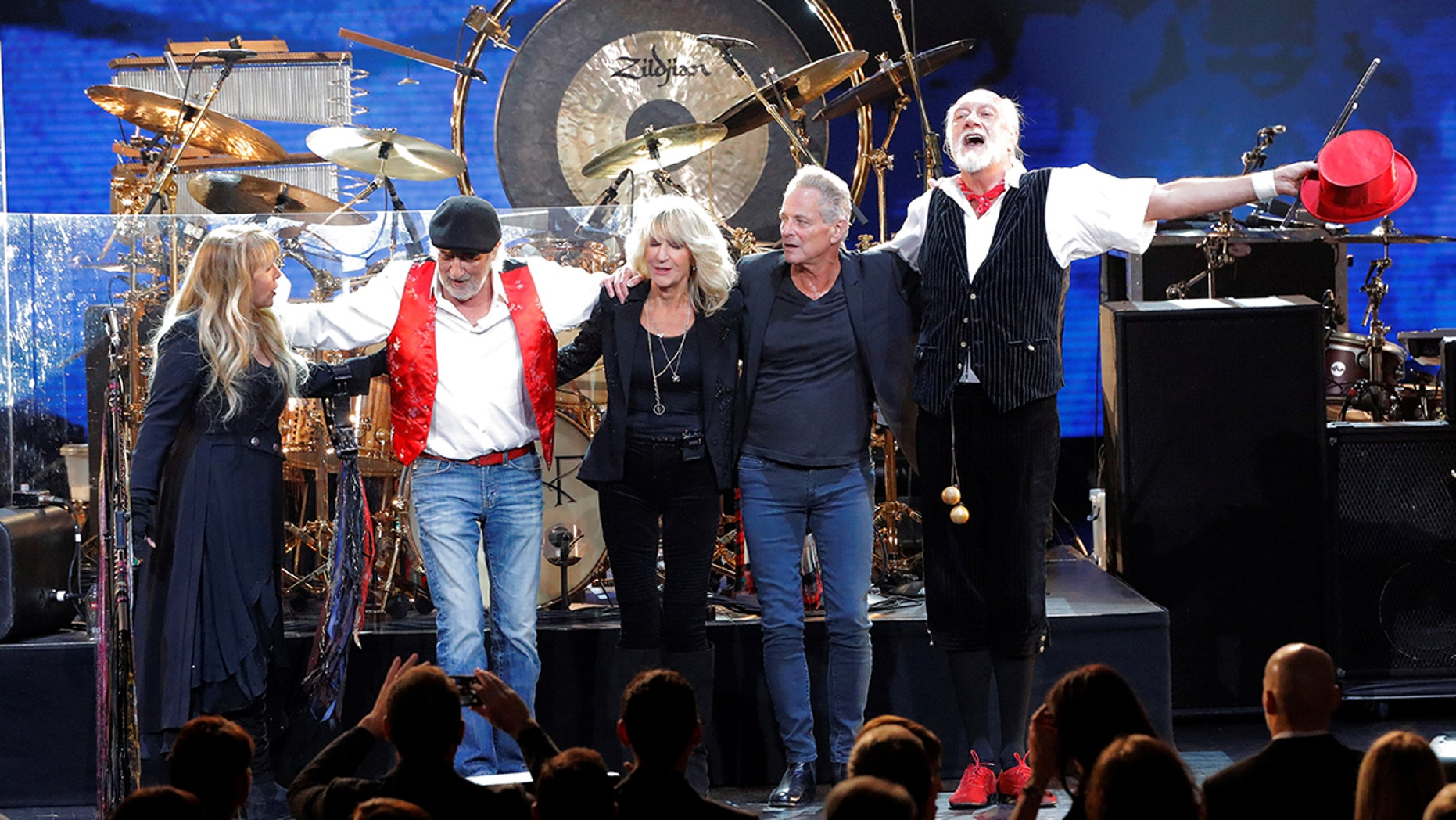 Stevie Nicks, John McVie, Christine McVie, Lindsey Buckingham, and Mick Fleetwood of the group Fleetwood Mac react after performing during the 2018 MusiCares Person of the Year show honoring Fleetwood Mac at Radio City Music Hall in Manhattan. Buckhingham is now suing his former bandmates for kicking off thier tour. <br>