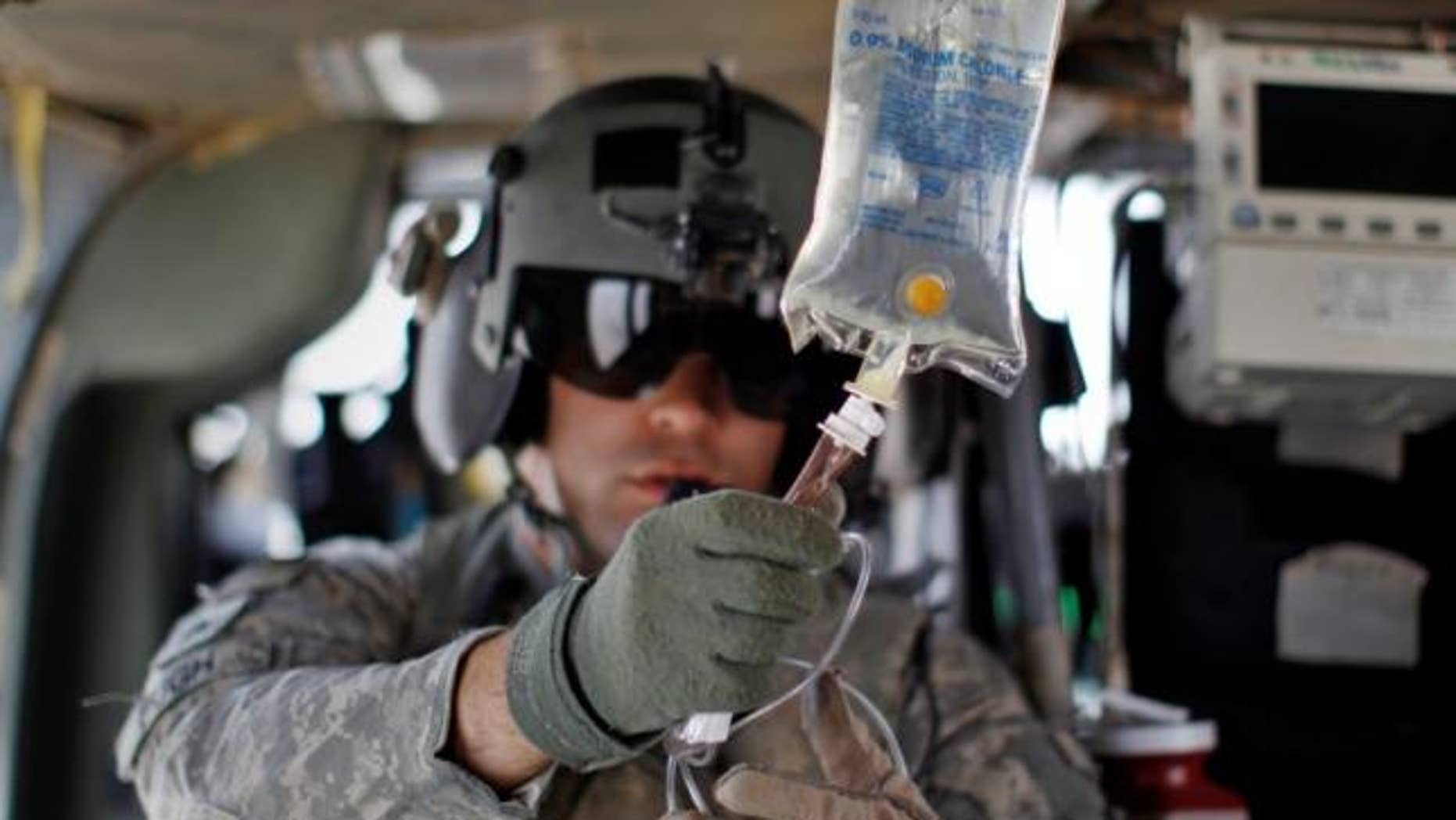 Aug. 17, 2010: Flight medic U.S. Army Sgt Ian Bugh prepares an IV drip as his medevac helicopter team flies to pick up a wounded Marine, near the town of Marjah in Helmand Province.