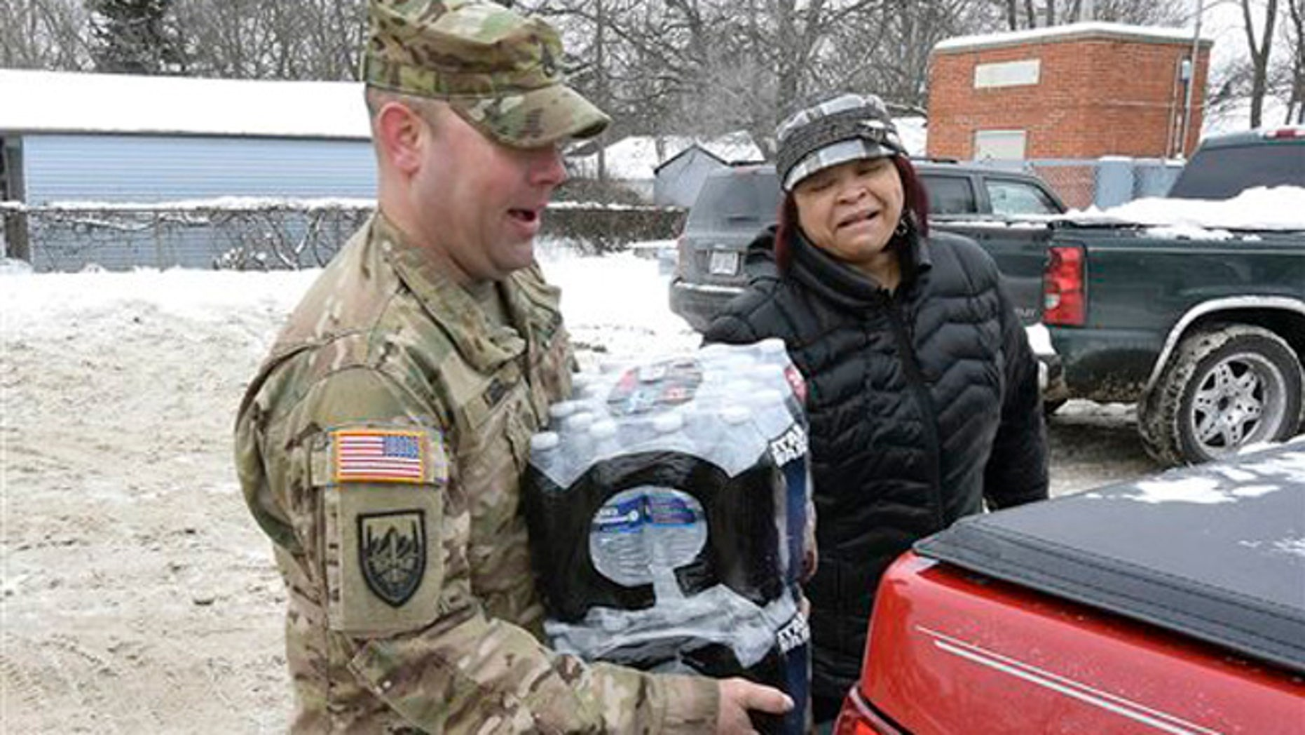 Michigan Sgt. Steve Kiger, left, carries cases of water for a Flint resident, Wednesday Jan 13, 2016 in Flint, Mich. (Dale G. Young/Detroit News via AP)