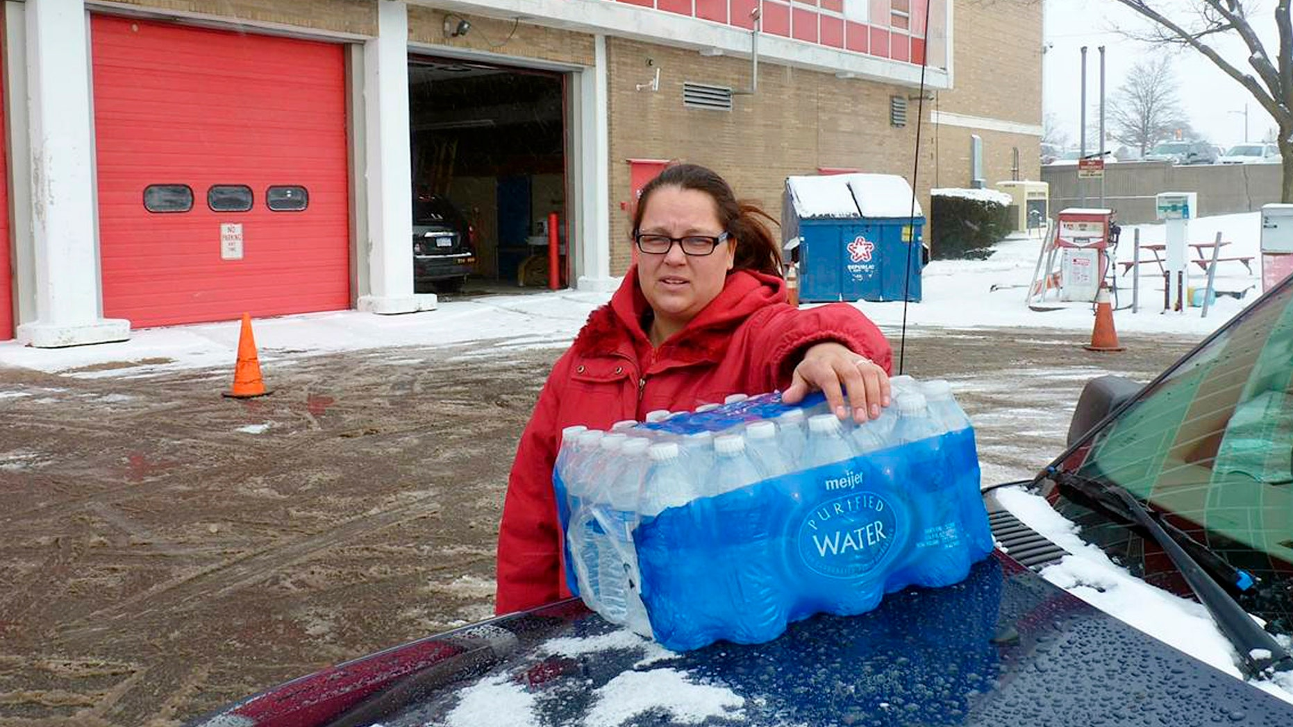 Rabecka Cordell picks up a case of bottled water outside the fire station in Flint, Mich.
