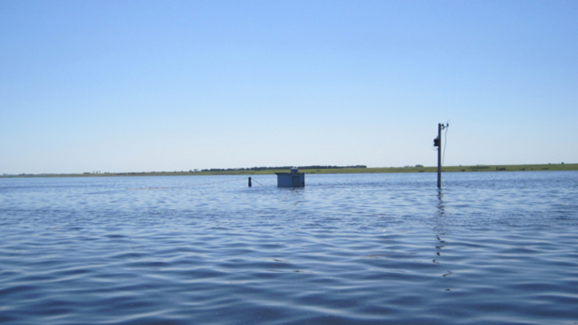 July 5, 2011: This handout photo provided by the US Geological Survery (USGS), taken near Westhope, N.D., shows the Souris River at the peak for the great Souris River flood of 2011, with equipment stored in cooler bolted to roof of gage house because water level was above gage house shelf.