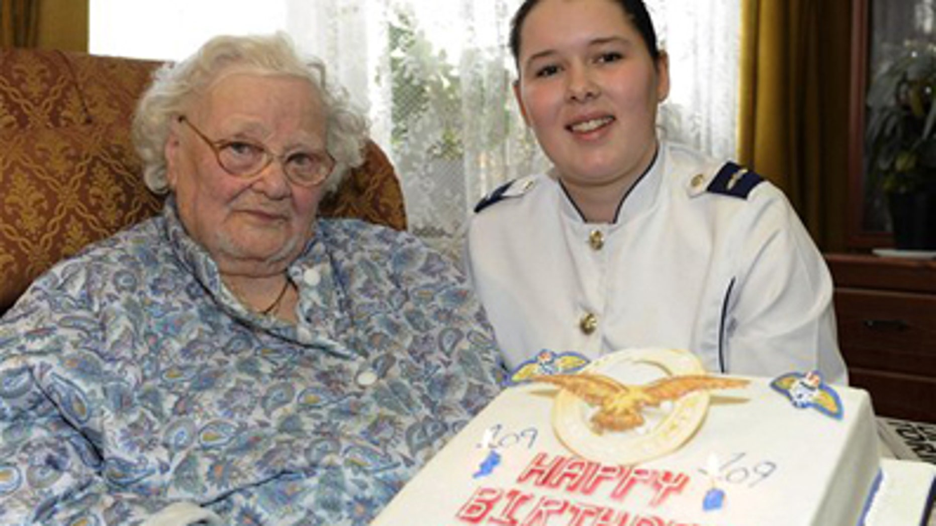 In this Feb. 19, 2010 photo released by the British Ministry of Defense, MOD, shows Florence Green, left, on her 109th birthday being presented with a birthday cake by LAC Hannah Shaw on behalf of the RAF at her home in King's Lynn, east England. Florence Green, the world's last known veteran of World War I, has died at the age of 110, the care home where she lived said Tuesday.