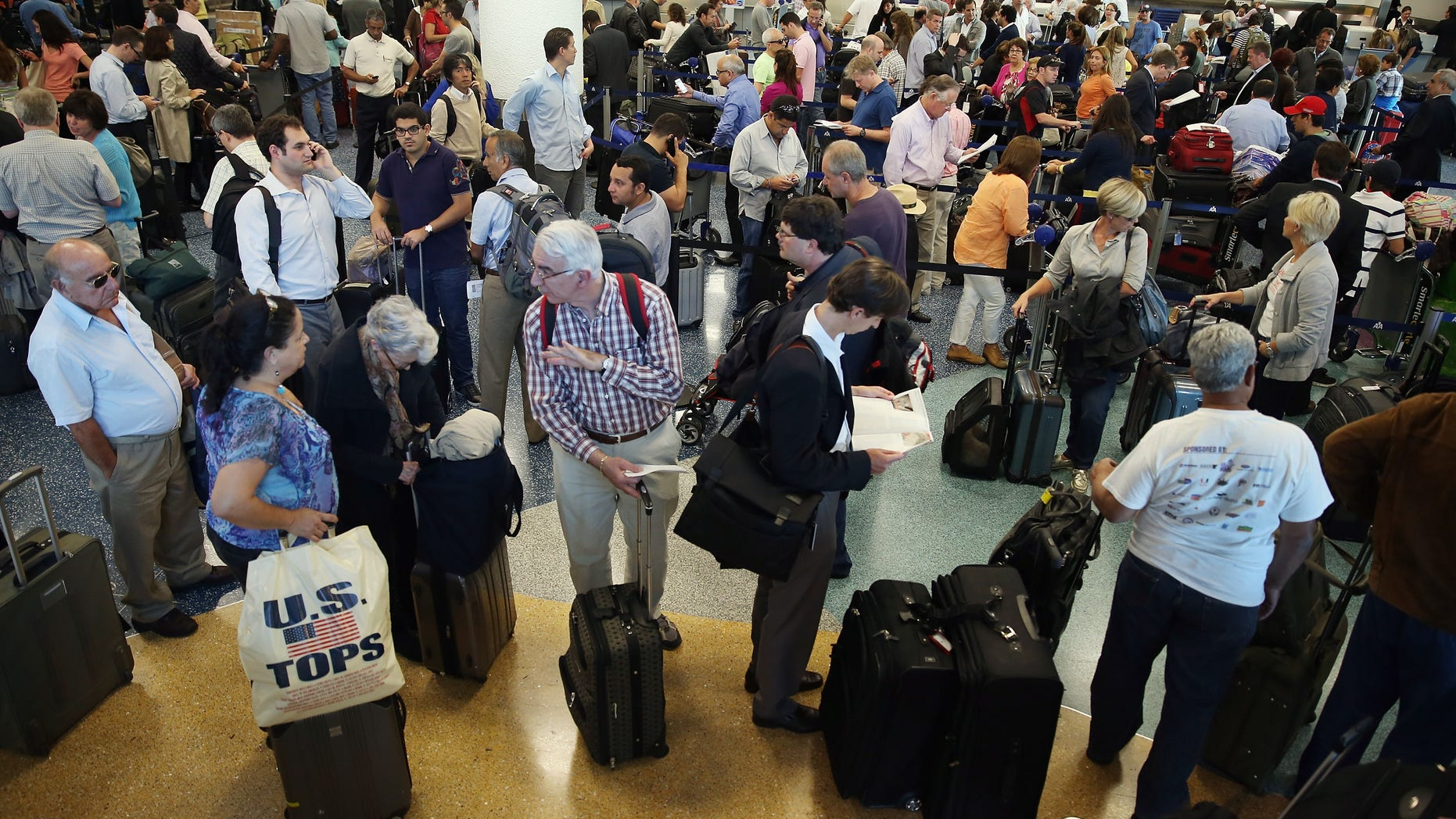Passengers wait in line at Miami International Airport on April 16, 2013 in Miami, Florida. (Photo by Joe Raedle/Getty Images)