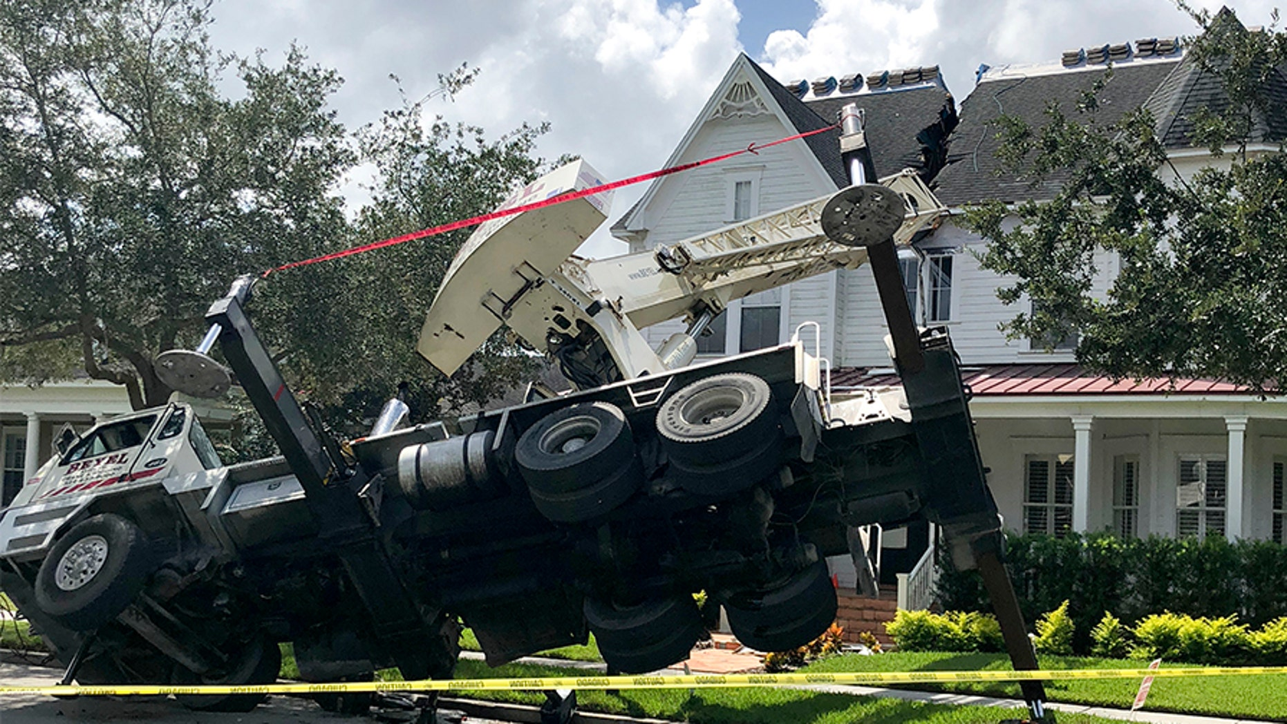 This photo released by the Orlando Fire Department shows a truck carrying a crane tipped over, damaging a house in Orlando, Fla., on Tuesday.