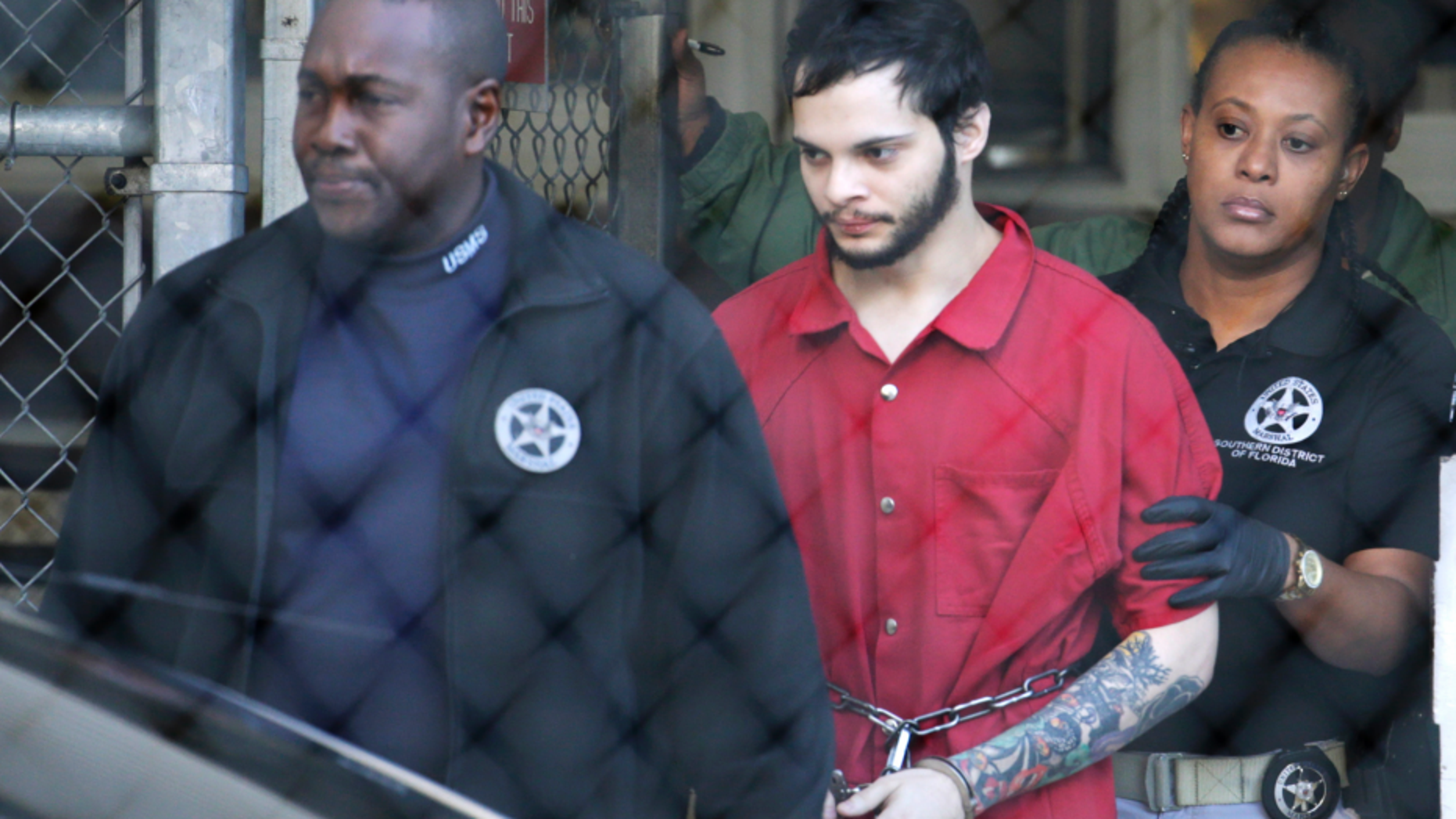 Law enforcement officers escort Esteban Santiago, the suspect in a deadly 2017 shooting at Fort Lauderdale-Hollywood International Airport in Florida.