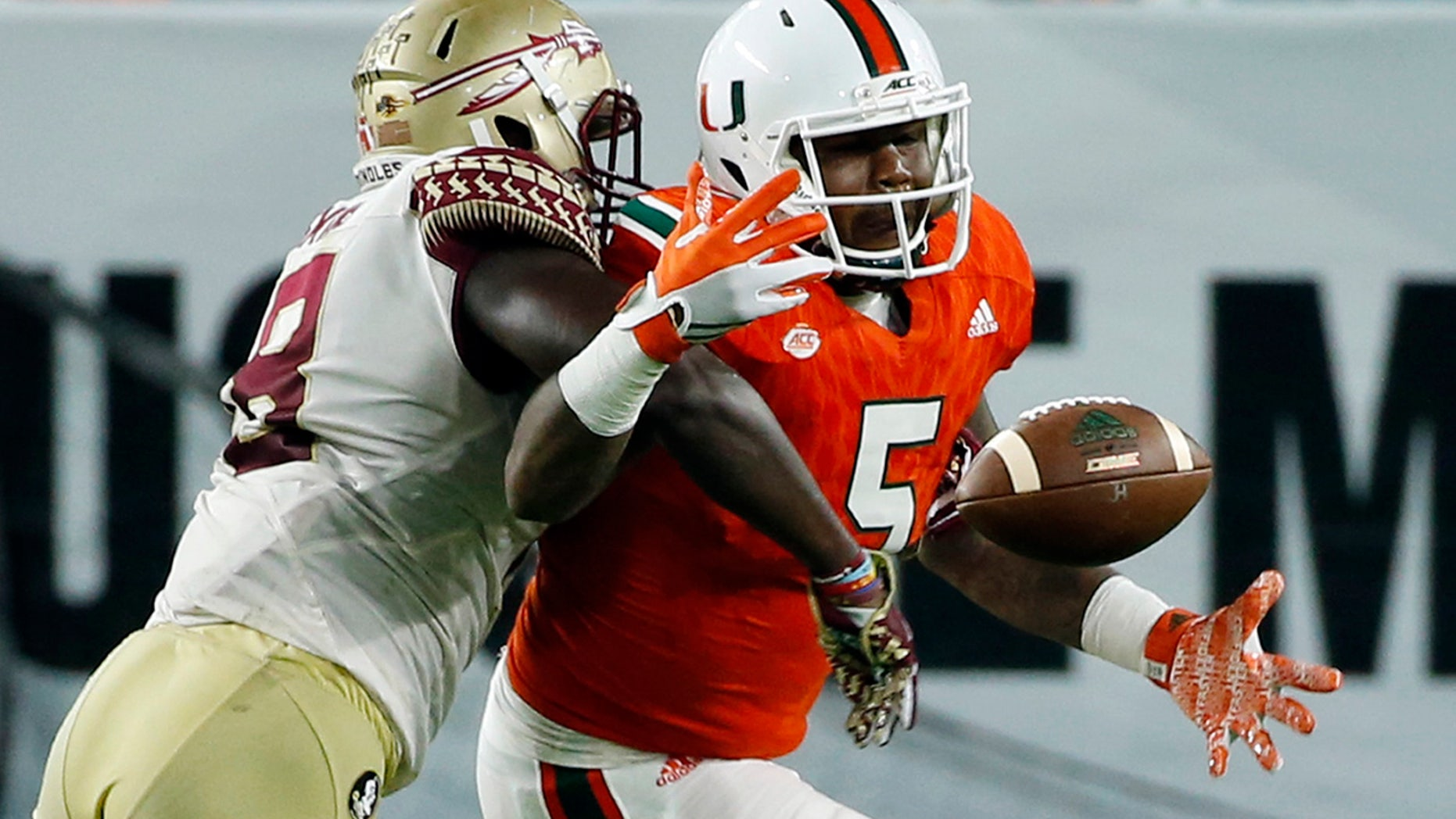 Miami Hurricanes tight end Standish Dobard (5) can't hold on to the ball as Florida State linebacker Ro'Derrick Hoskins (18) defends during the second half of an NCAA college football game, Saturday, Oct. 8, 2016, in Miami Gardens. (AP Photo/Wilfredo Lee)