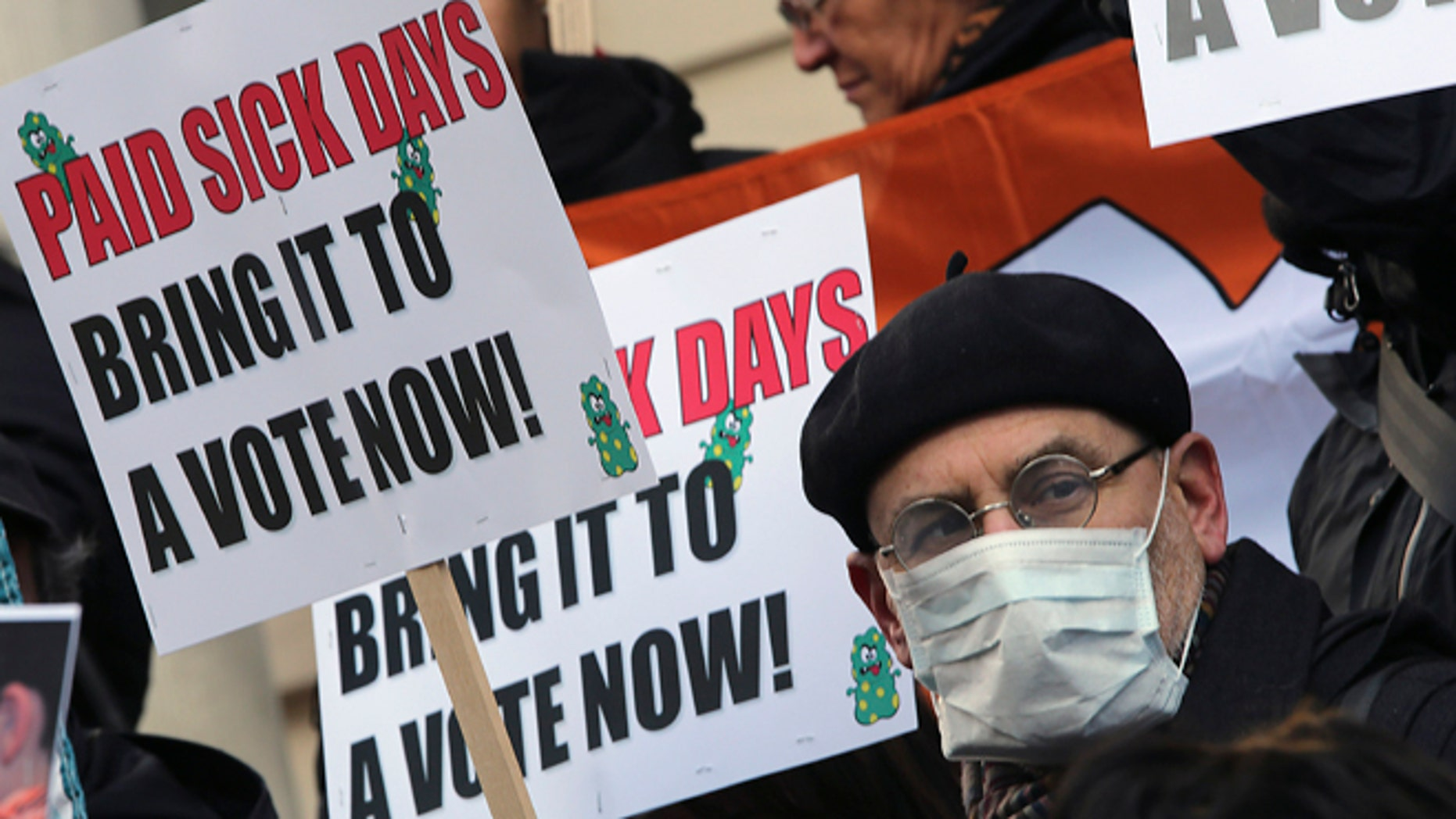 Jan. 18 2013 : In this photo, activists hold signs during a rally at New York's City Hall to call for immediate action on paid sick days legislation in light of the continued spread of the flu.