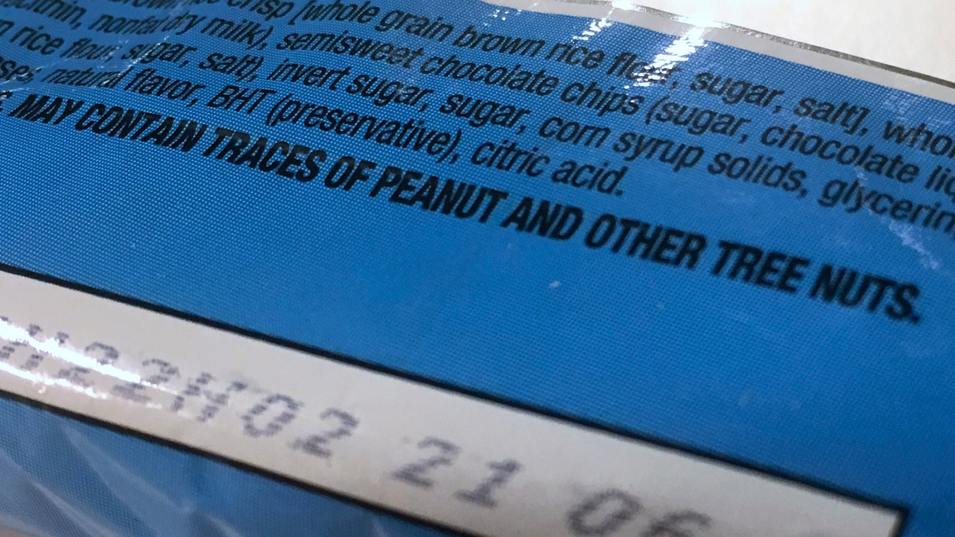 """This Nov. 30, 2016, photo shows part of a food label that states the product """"may contain traces of peanut and other tree nuts"""" as photographed in Washington. A new report says the hodgepodge of warnings that a food might accidentally contain a troublesome ingredient is confusing to people with food allergies, and calls for a makeover. The report from the prestigious National Academies of Sciences, Engineering and Medicine said it's time for regulators and the food industry to clear consumer confusion with labels that better reflect the level of risk. (AP Photo/Jon Elswick)"""