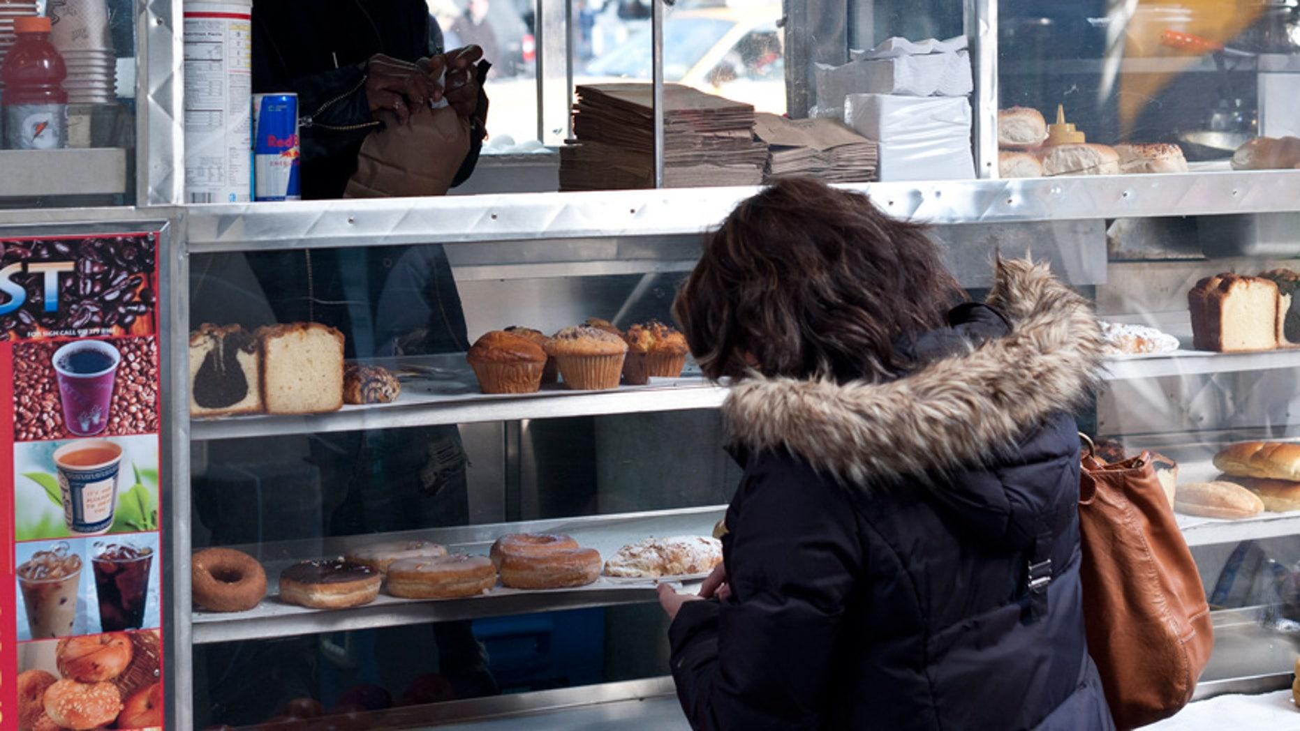 A vendor sells baked goods at a New York City food cart.