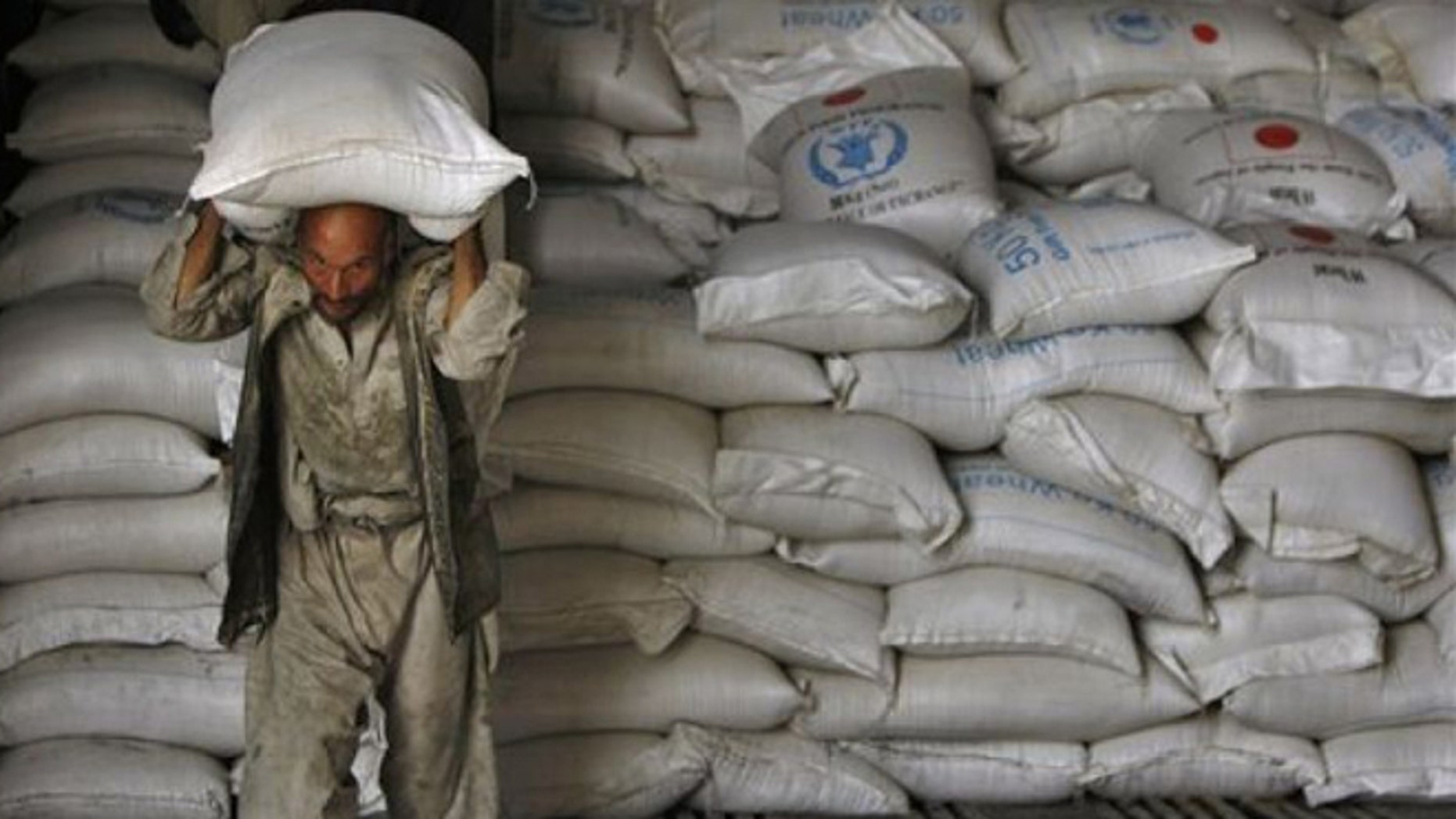 June 27: An Afghan man carries a sack of wheat from a UN World Food Programme warehouse. Due to budget constraints, on June 27th the UN announced that it would be force to cut food assistance to more than 3 million Afghan people. (AP)