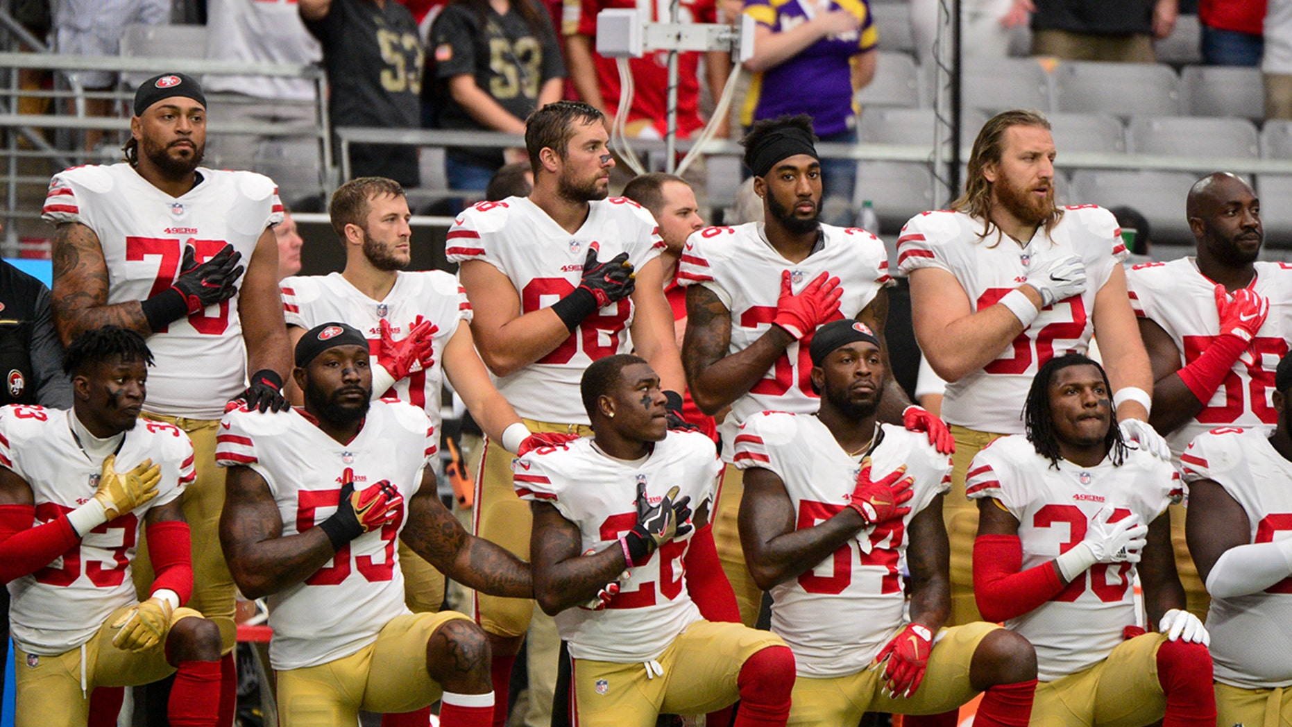 Oct 1, 2017; Glendale, AZ, USA; Members of the San Francisco 49ers kneel during the National Anthem prior to a game against the Arizona Cardinals at University of Phoenix Stadium. Mandatory Credit: Matt Kartozian-USA TODAY Sports - 10321248