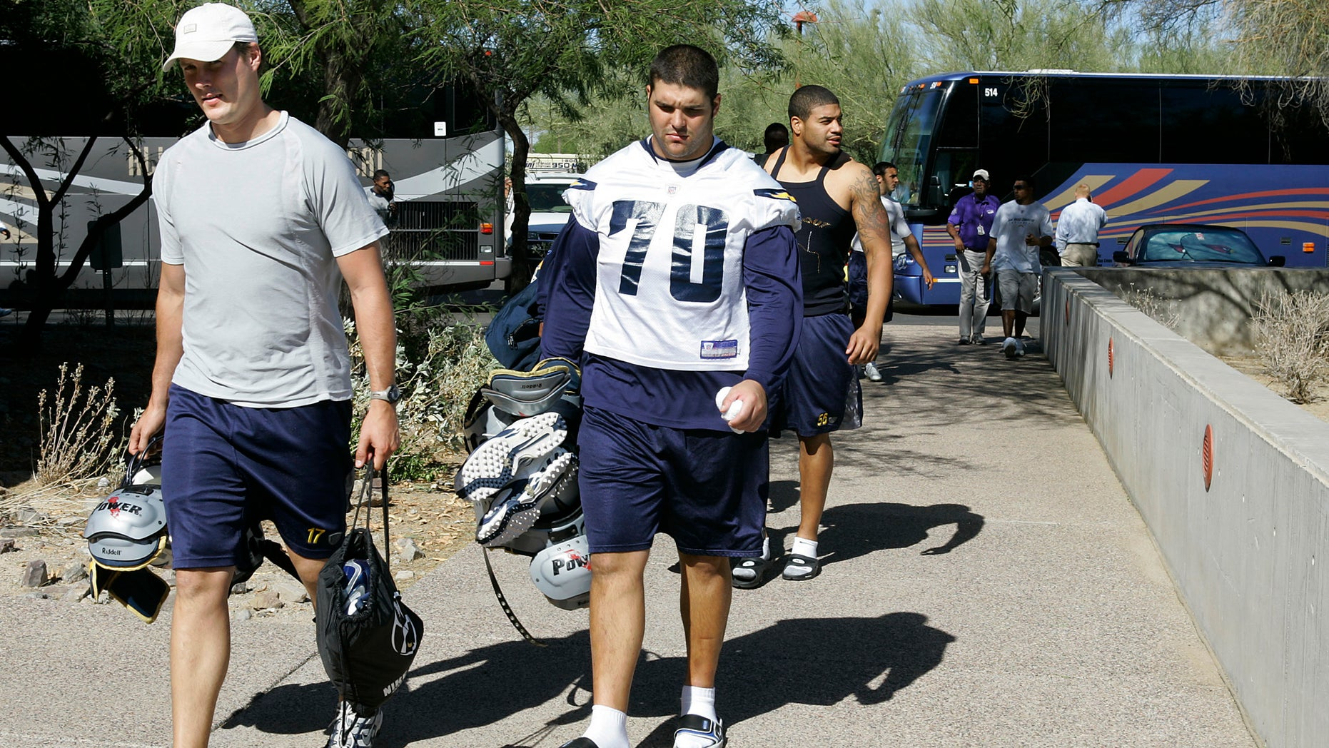 FILE - In this Oct. 24, 2007 file photo, San Diego Chargers' Philip Rivers, left, Shane Olivea (70) and Shawne Merriman, right, arrive for practice with teammates and coaches at the Arizona Cardinals training facility  in Tempe, Ariz.   Olivea, whose NFL career fell apart because of a painkiller addiction says he wants to become a college coach and help others avoid similar pitfalls now that he's clean and has a degree. (AP Photo/Ross D. Franklin)
