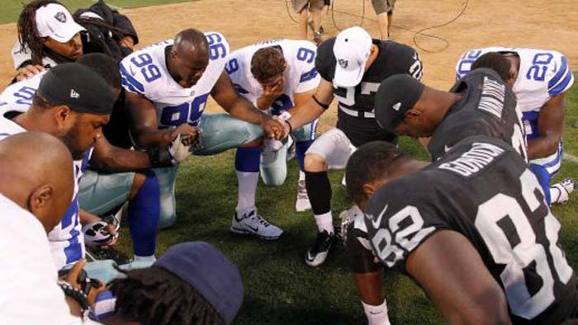 Praying after games is a football tradition, as seen here following an NFL contest between the Dallas Cowboys and the Oakland Raiders. (AP)