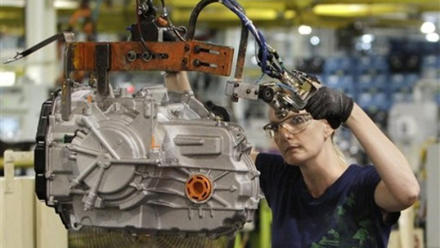 In this June 9 file photo, a line worker moves a transmission from the assembly line to a pallet at the Ford Van Dyke Transmission Plant in Sterling Heights, Mich.