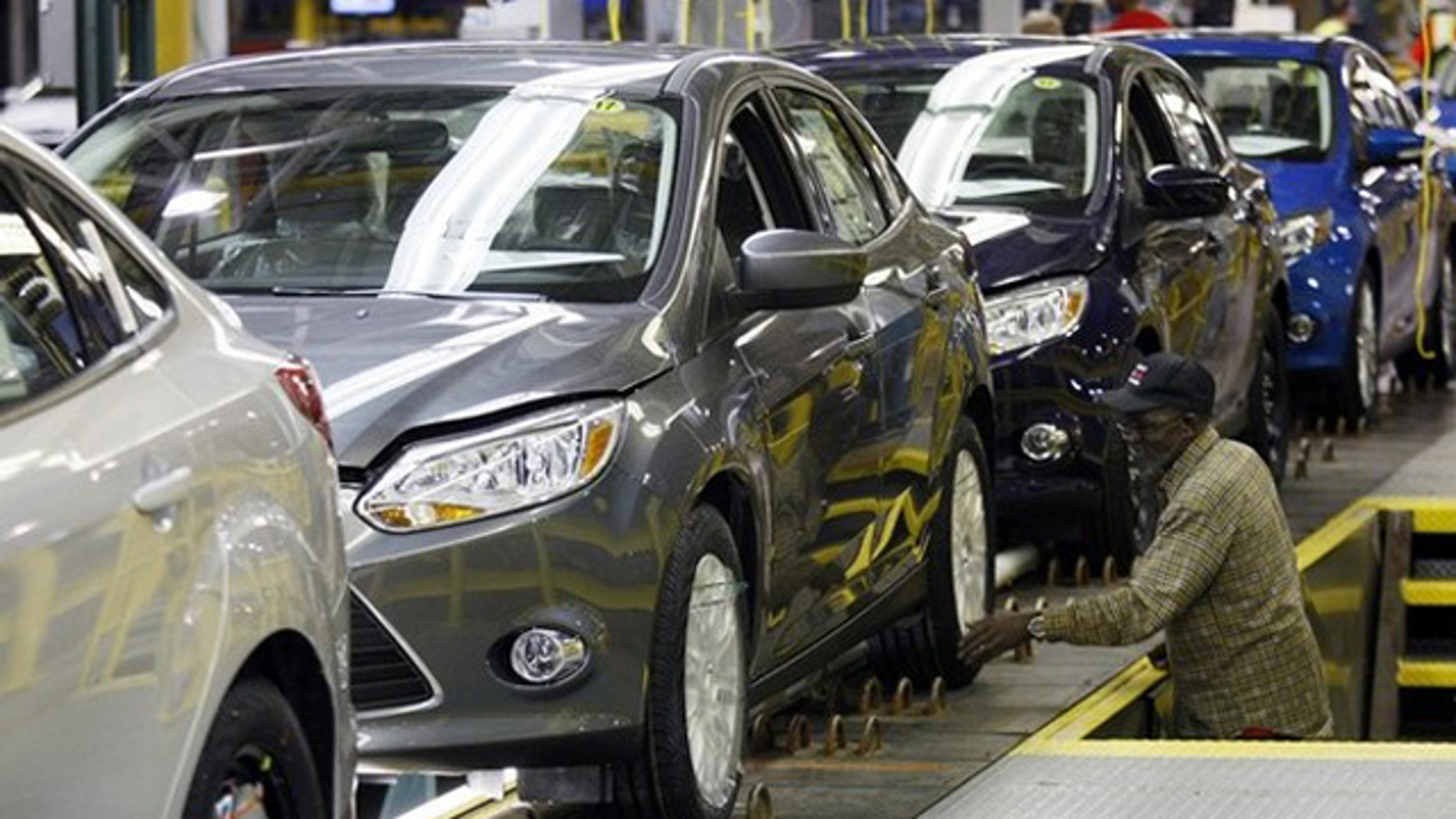 A Ford employee works on the final production line of the 2012 Ford Focus at Michigan Assembly Plant in Wayne, Mich., March 17.