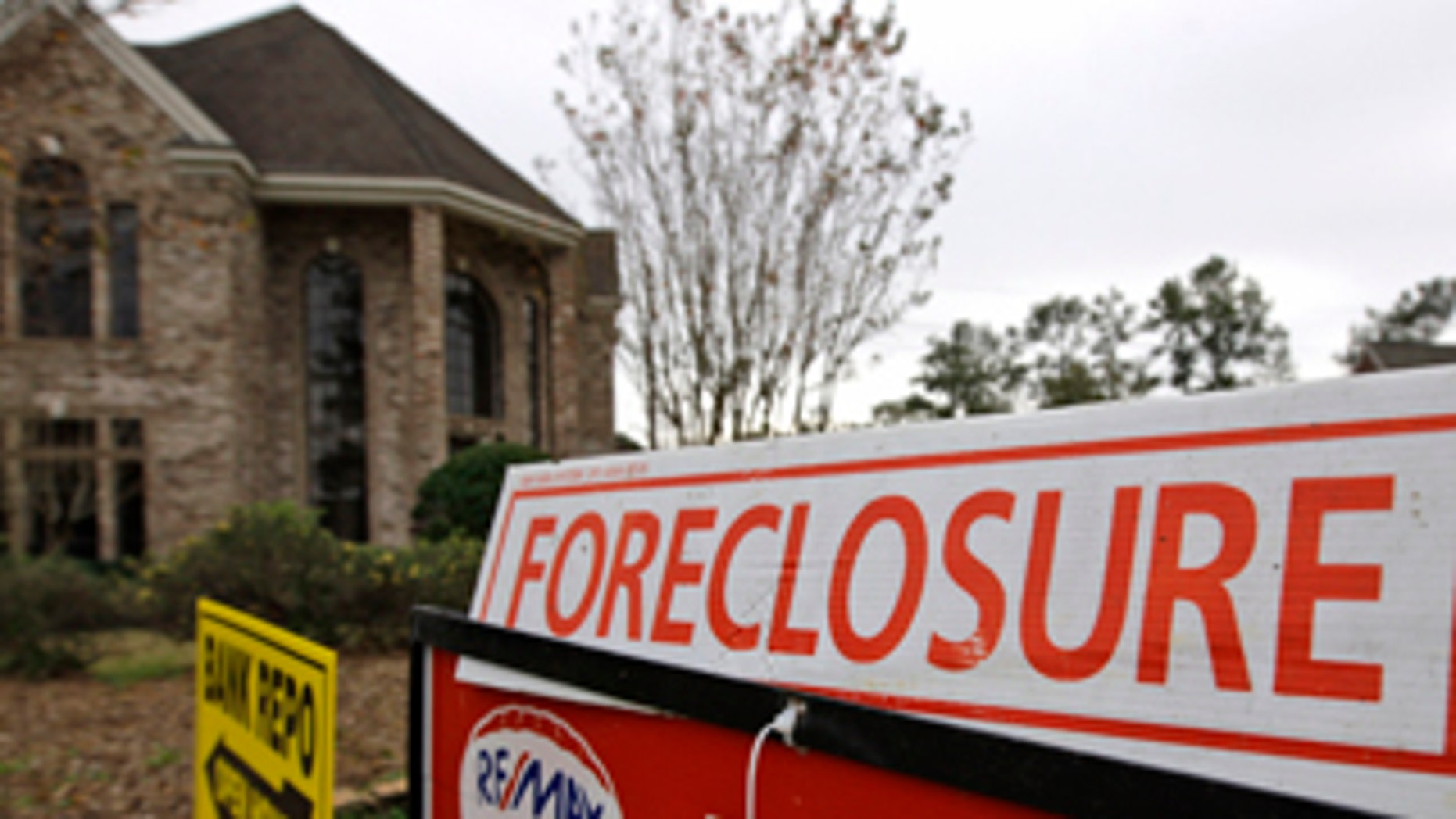 Jan. 20, 2009: Bank repo, foreclosure and for sale signs sit outside a foreclosed home in Houston.