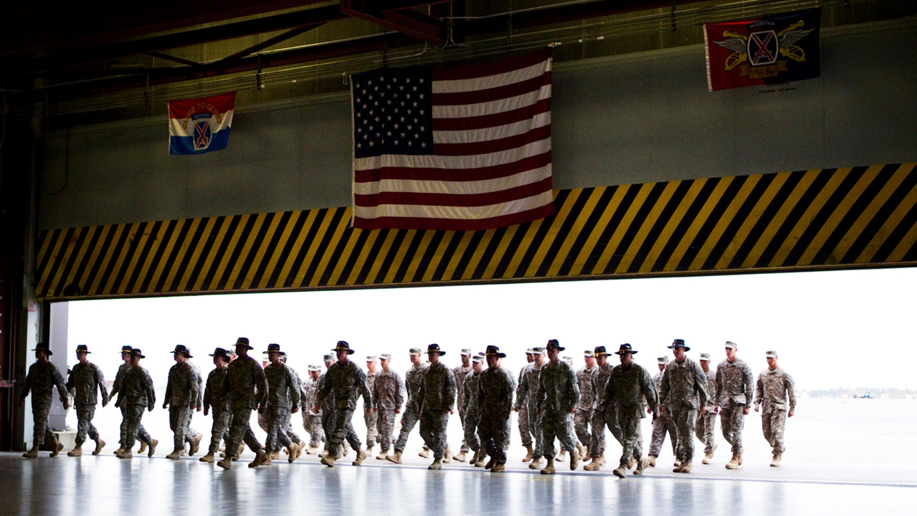 Soldiers from the 10th Combat Aviation Brigade walk into a ceremony at Fort Drum as they return from a yearlong tour in Afghanistan.