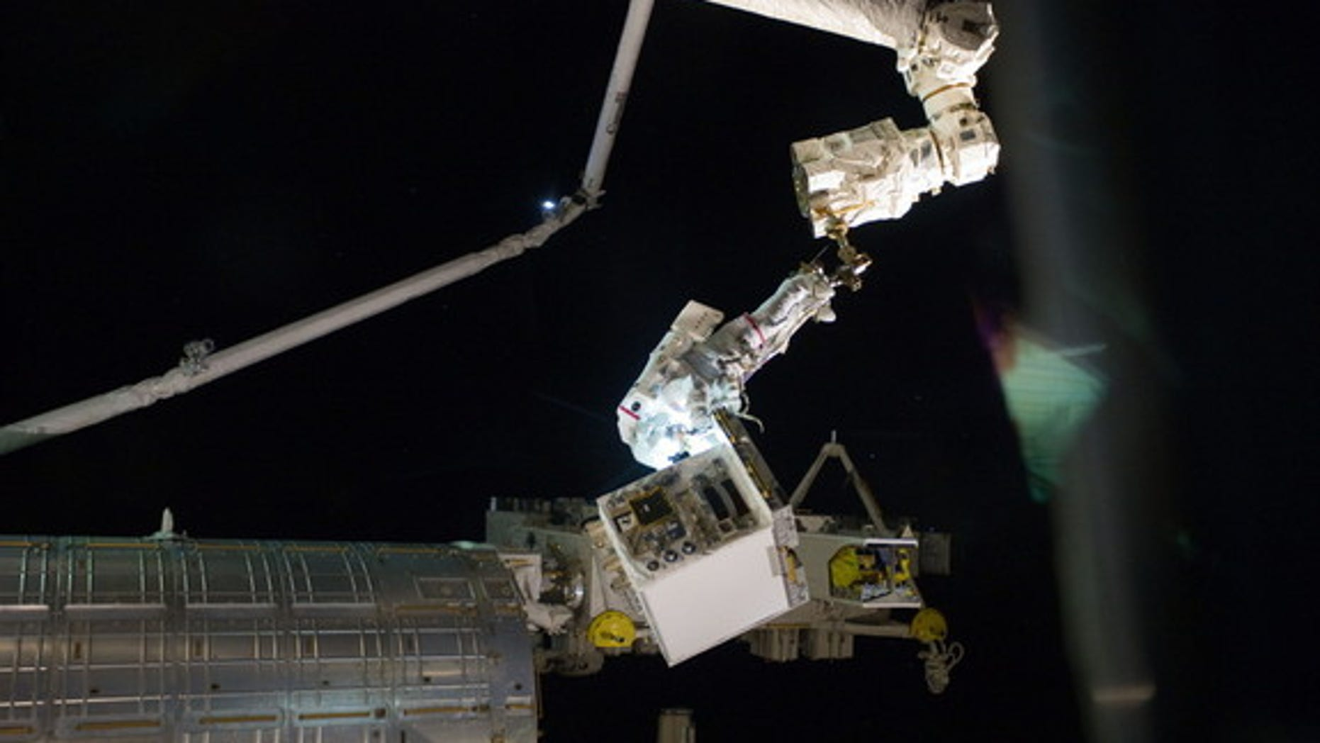 With his feet secured on a restraint on the space station's Canadarm2, NASA astronaut Mike Fossum holds the Robotics Refueling Mission payload, which was the focus of one of the primary chores accomplished on a six and a half hour spacewalk on