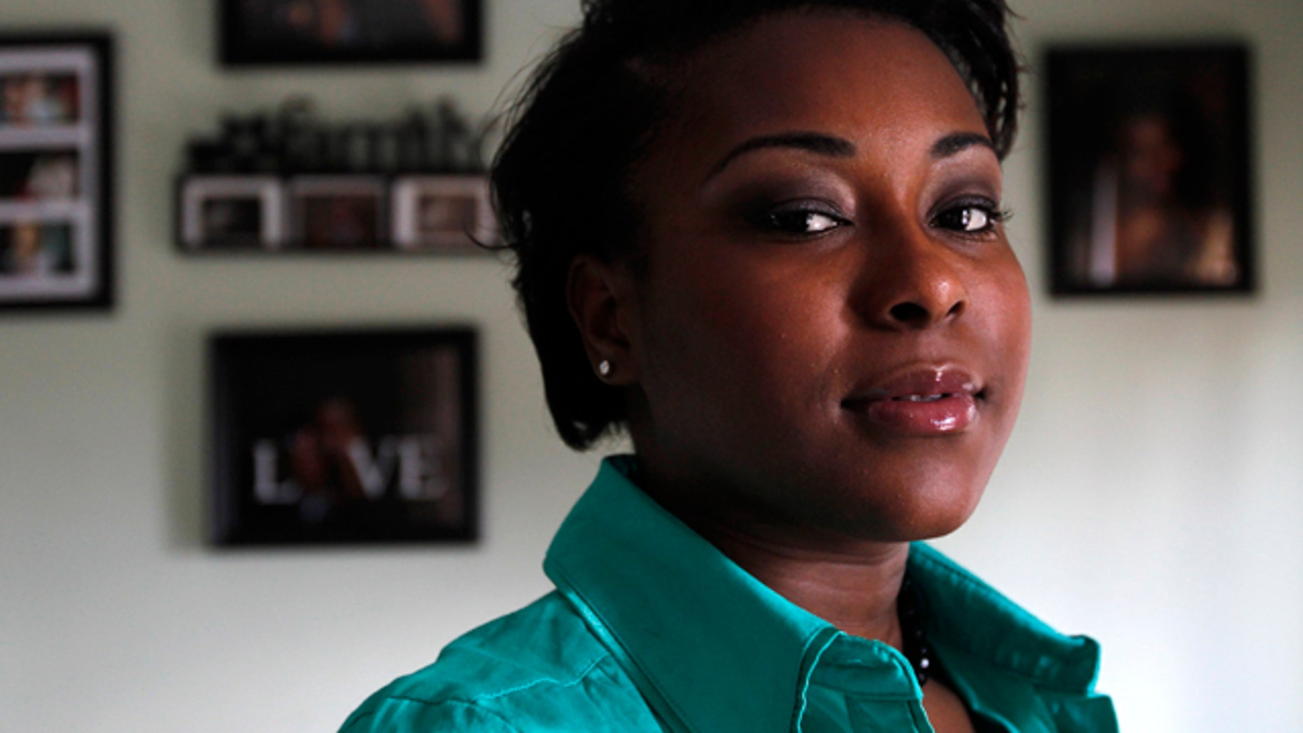 Oct. 5: Dee Saint Franc, 21, of Providence, R.I., stands for a portrait in front of family photos in her home. Saint Franc left the Rhode Island foster care system at age 18 eager to start life on her own. She went to a Verizon store to buy a phone and instead learned that someone had used her identity to rack up $3,000 worth of delinquent bills at Verizon dating back to 1998.