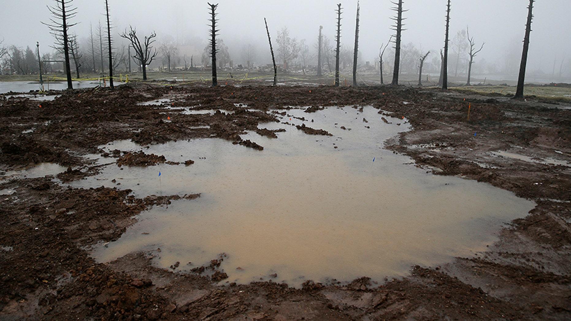 Rain water pools where a Fountaingrove neighborhood home once stood Monday in Santa Rosa, Calif.