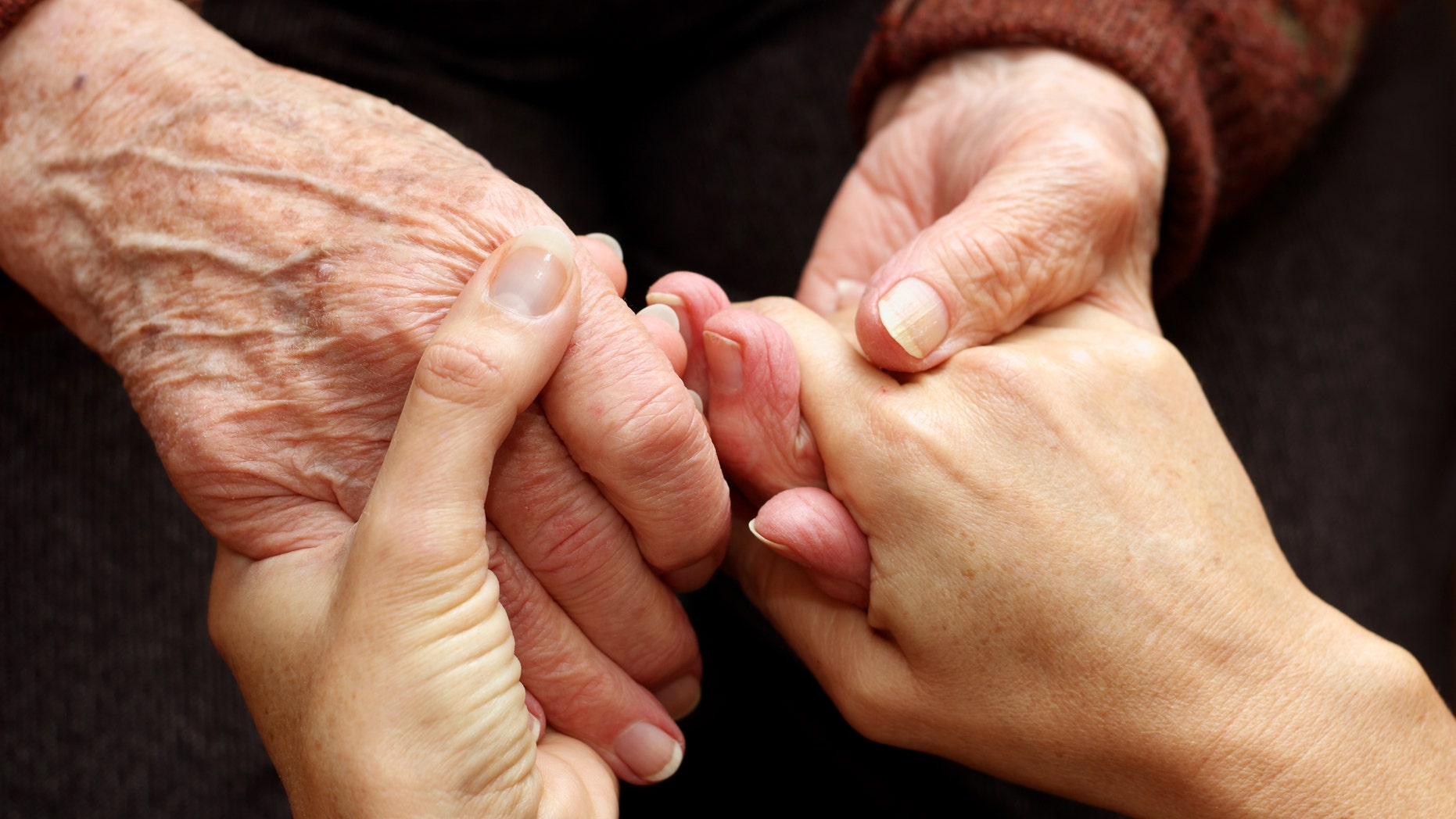 The hands of a young woman takes those of an older person as a sign of support and help