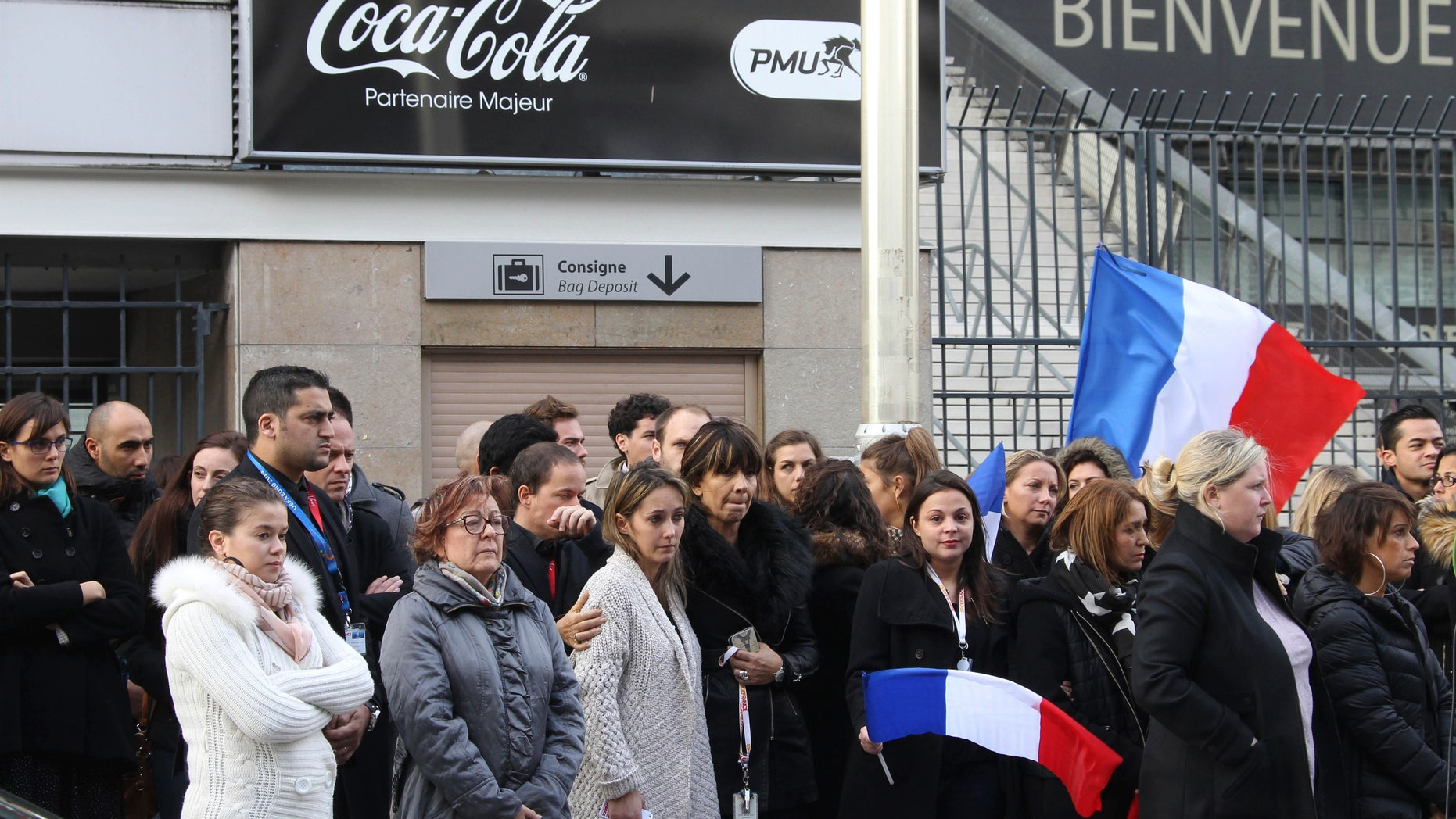 People stand for a minute of silence near the Stade de France stadium in Saint Denis, outside Paris.