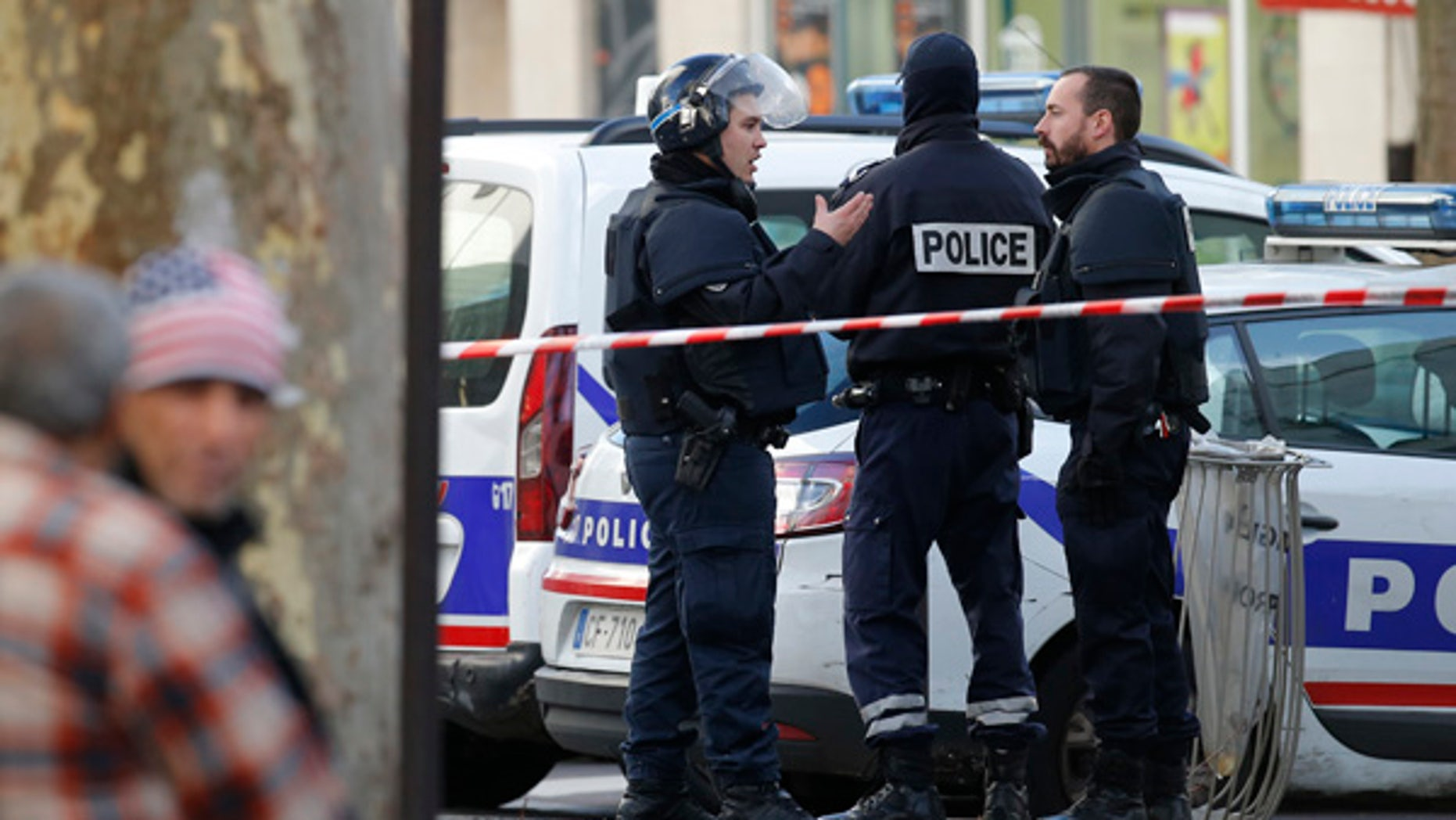 Jan. 7, 2016: Police officers secure the area after a fatal shooting took place at a police station in Paris.