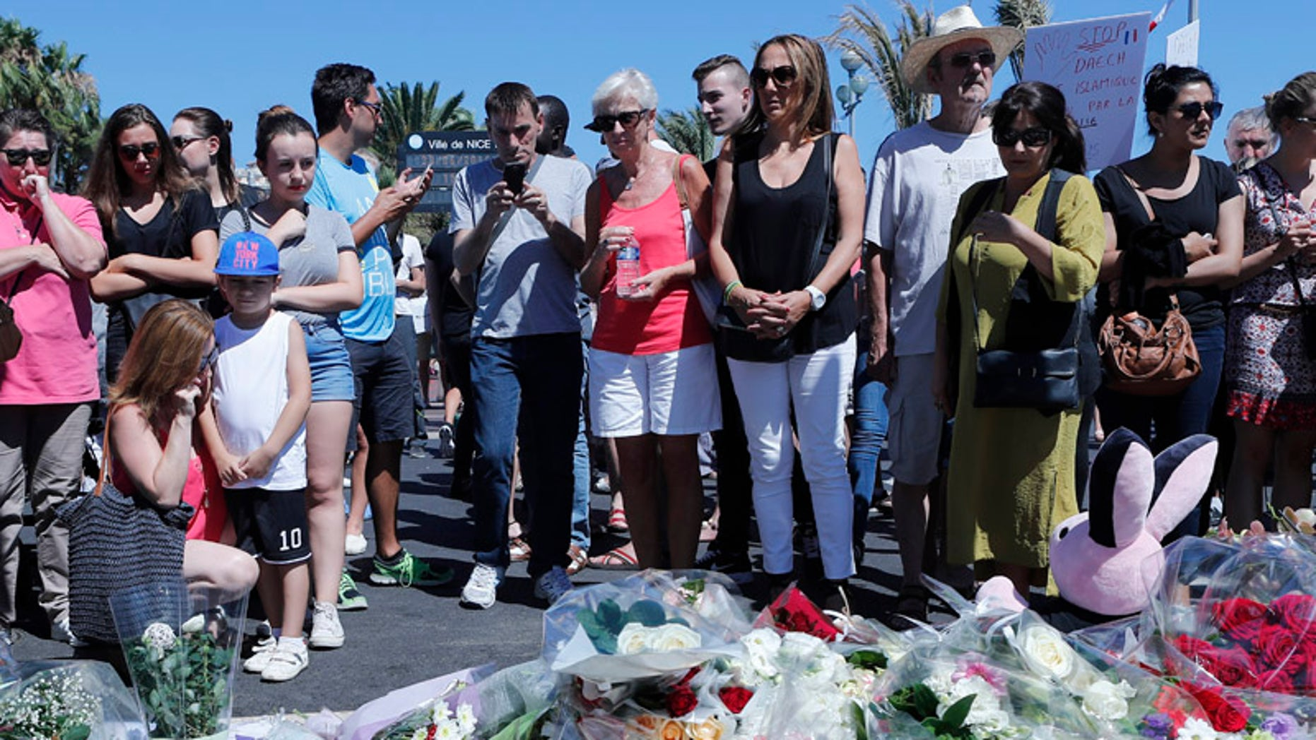 People stand by flowers laid near the scene where a truck mowed through revelers in Nice, southern France, Friday, July 15, 2016.  A large truck mowed through revelers gathered for Bastille Day fireworks in Nice, killing more than 80 people and sending people fleeing into the sea as it bore down for more than a mile along the Riviera city's famed waterfront promenade.  (AP Photo/Francois Mori)