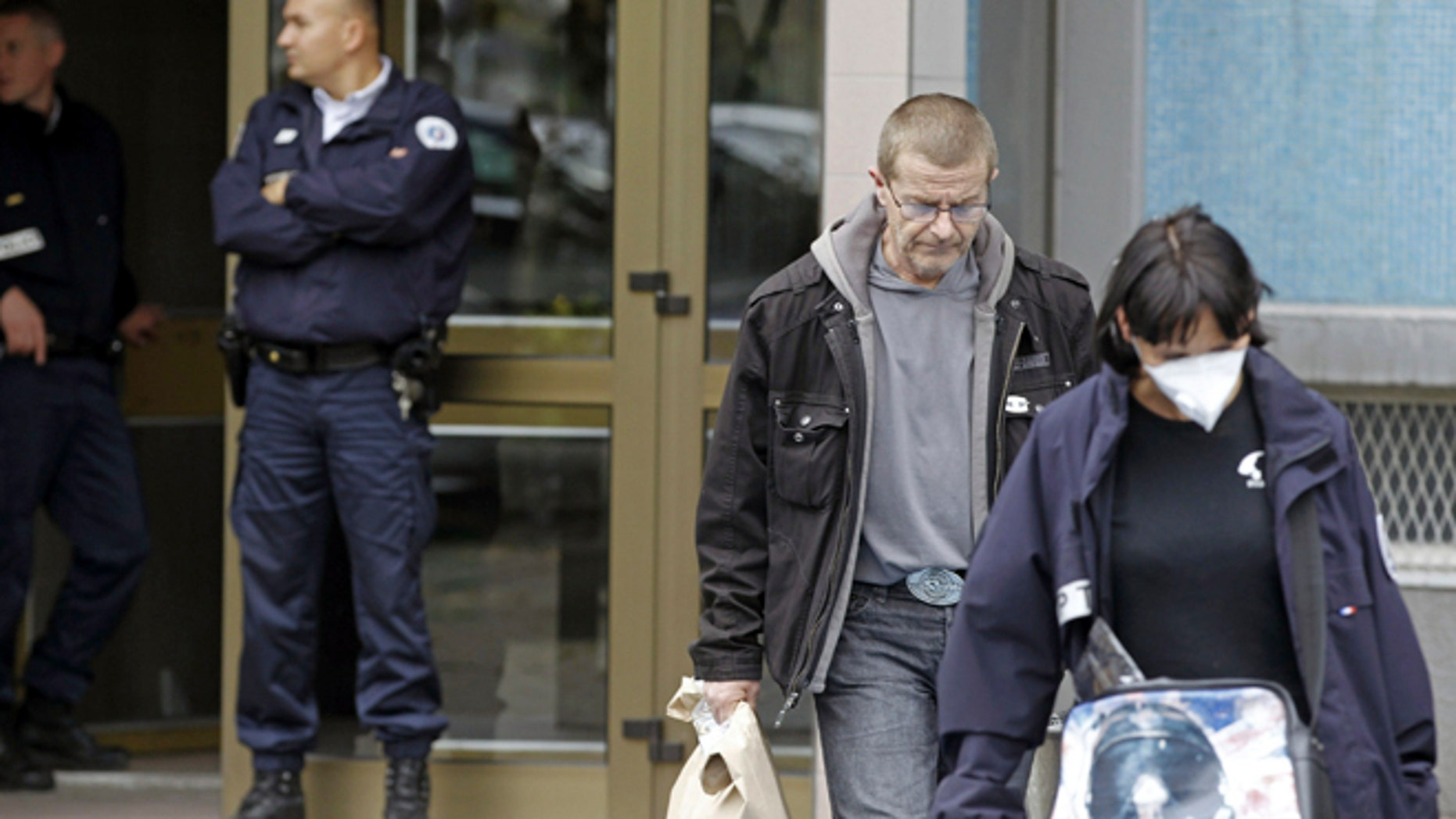 Oct. 6, 2012: French police officers, left, stand guard at the entrance of a building in Strasbourg, France, as plainclothed policemen carrying clues, right, leave, after a suspect was shot dead for firing at police.