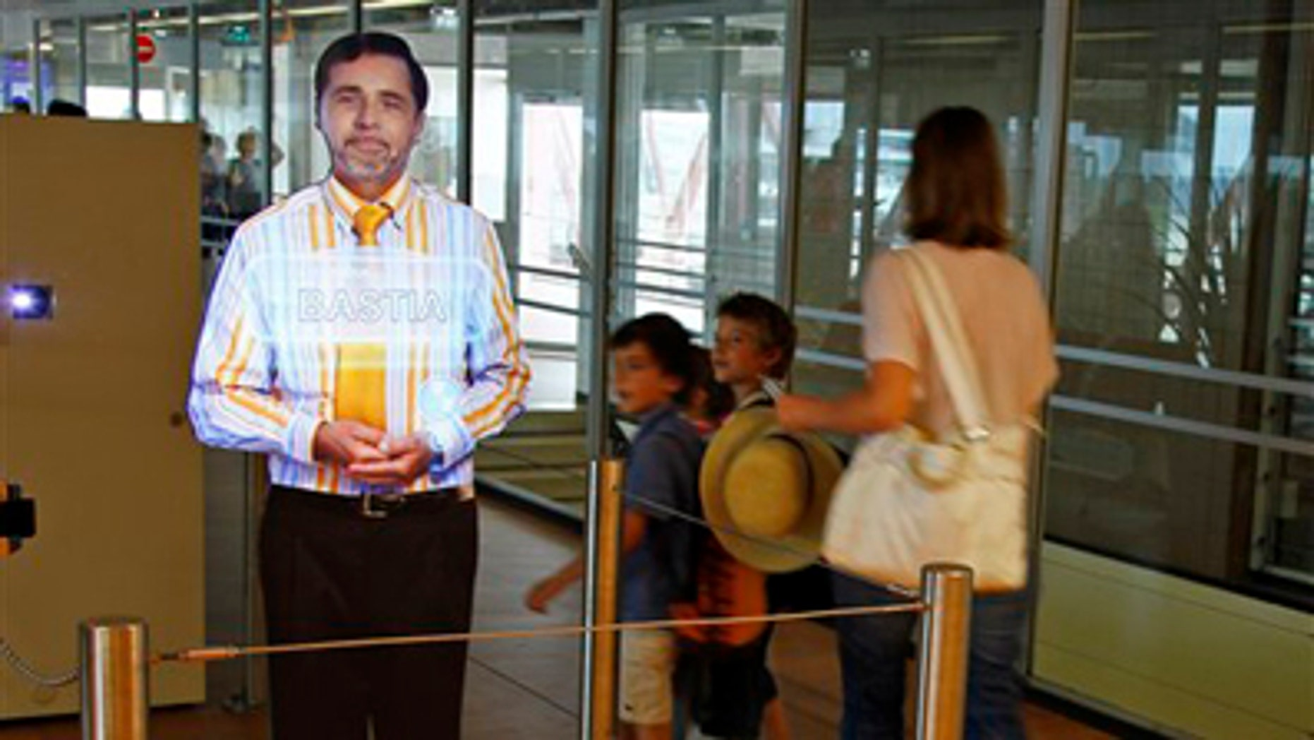 """Aug. 18: An airport experimenting """"virtual"""" boarding agent, left, is displayed at Paris' Orly airport, on the southern outskirts of Paris. The pilot project began last month, and has so far been met with a mix of amusement and surprise by travellers, who frequently try to touch and speak with the strikingly life-like video images that greet them and direct them to their boarding gate."""