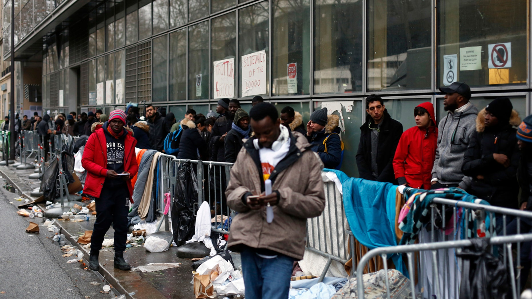 FILE - In this Dec.21, 2017 file photo, migrants queue outside a facility to apply for asylum, in Paris. French President Emmanuel Macron's government presents its first big immigration bill at Cabinet meeting Wednesday Feb.21, 2018. The government says the bill aims at accelerating expulsion of people who don't qualify for asylum and offering better conditions for those who are allowed to stay in the country. (AP Photo/Thibault Camus, File)