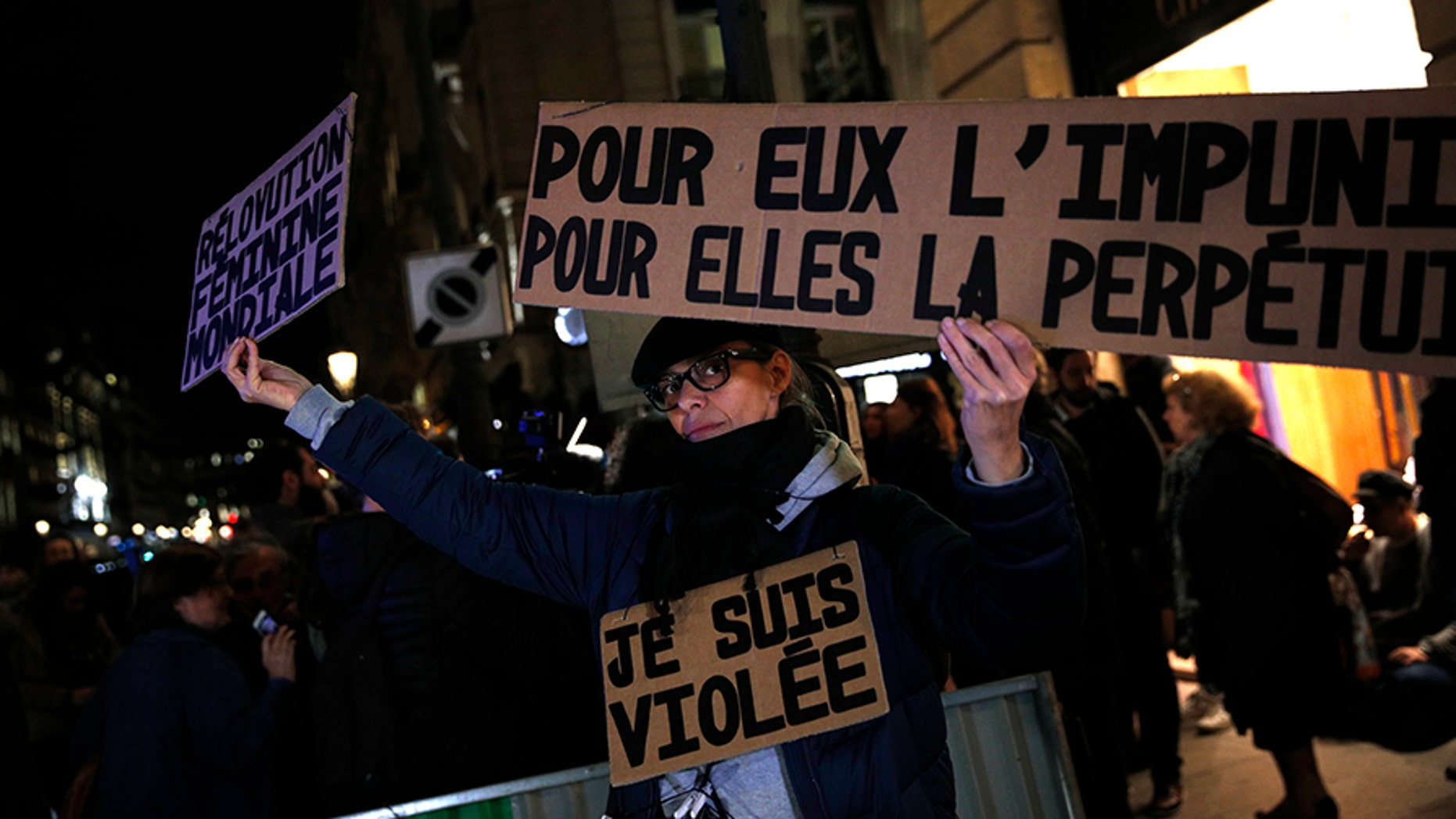 """An activist holds a banner reading: """"For him impunity, for her a life sentence,"""" during a protest in Paris. Activists have protested demanding that the age of consent be set at 15."""