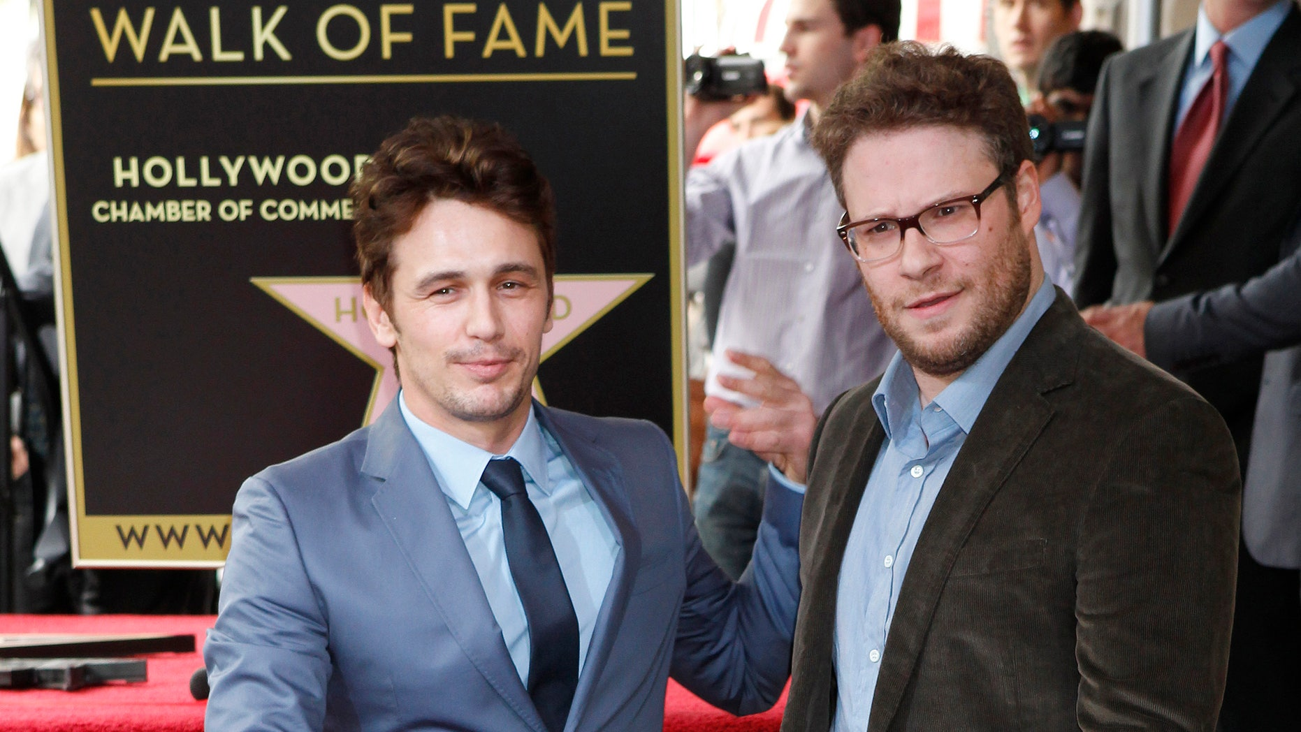 March 7, 2013. Actor James Franco (L) poses with his newly unveiled star on the Hollywood Walk of Fame, with actor Seth Rogen.