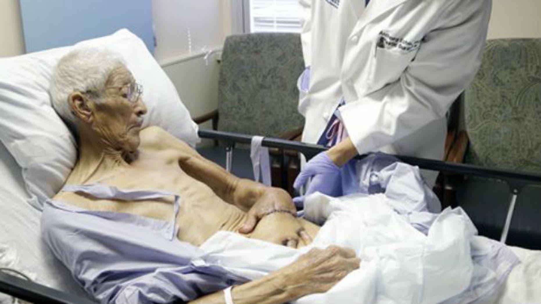 Plastic surgeon Anthony Echo, right, examines Frank Reyes' hand before surgery at Houston Methodist Hospital in Houston on Thursday, Aug. 27, 2015. (AP Photo/Pat Sullivan)