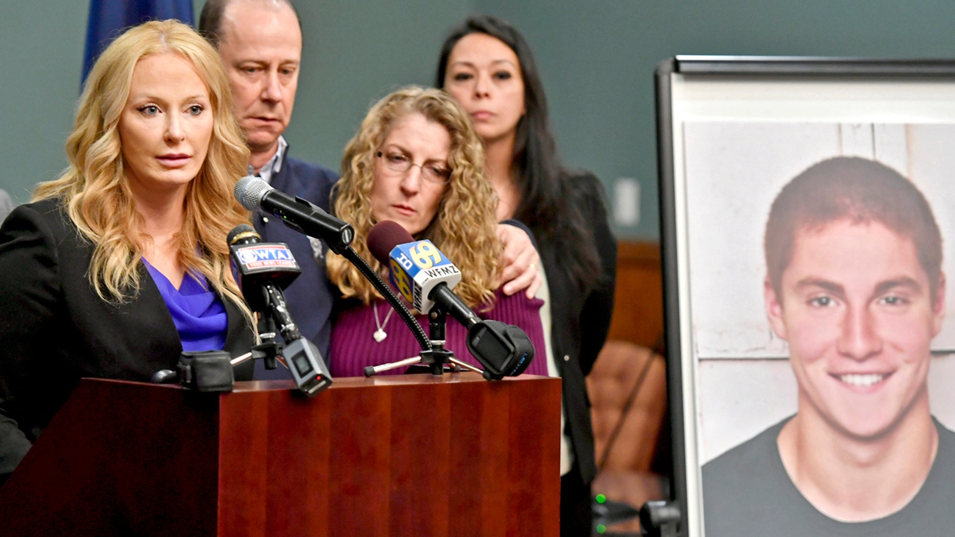 In this May 5, 2017, file photo, Centre County, Pa., District Attorney Stacy Parks Miller, left, announces findings an investigation into the death of Penn State University fraternity pledge Tim Piazza, seen in photo at right, as his parents, Jim and Evelyn Piazza, second and third from left, stand nearby during a news conference in Bellefonte, Pa.