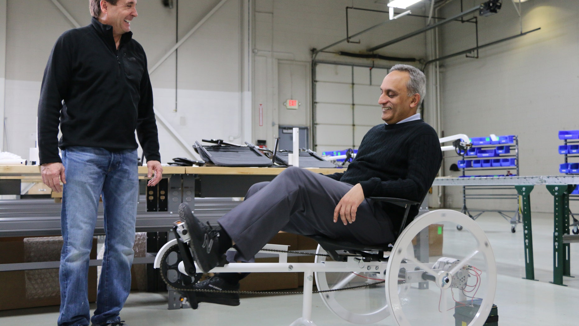 Living Essentials CEO Manoj Bhargava (R) pedals a Free Electric bike (Billions in Change LLC).