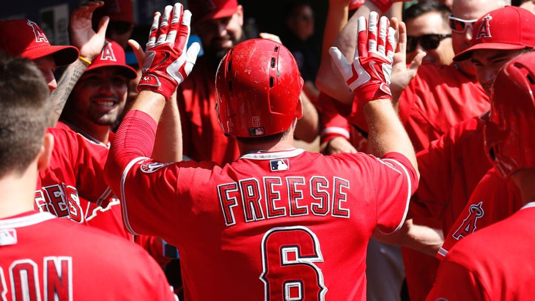 Oct 3, 2015; Arlington, TX, USA; Los Angeles Angels third baseman David Freese (6) celebrates his run with teammates against the Texas Rangers during the fifth inning of a baseball game at Globe Life Park in Arlington. Mandatory Credit: Jim Cowsert-USA TODAY Sports