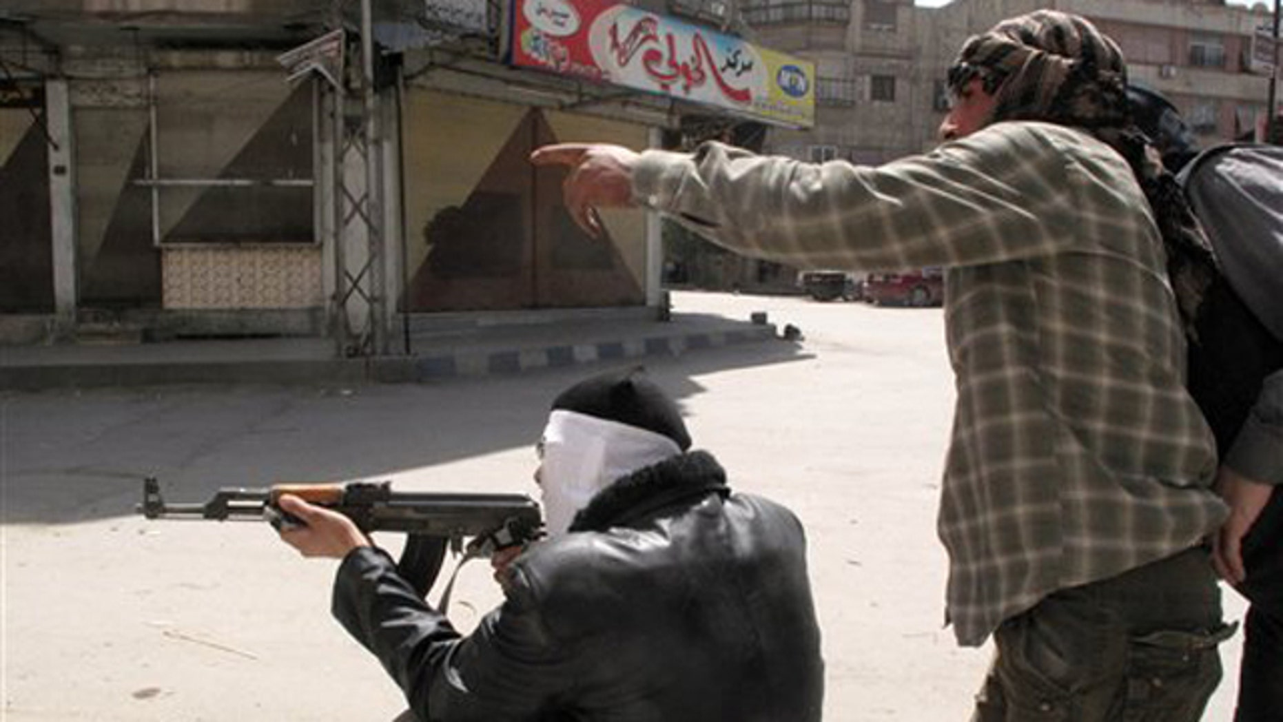April 6, 2012: In this photo, Free Syrian Army fighters try to spot a sniper during fighting with Syrian troops in a suburb of Damascus, Syria.