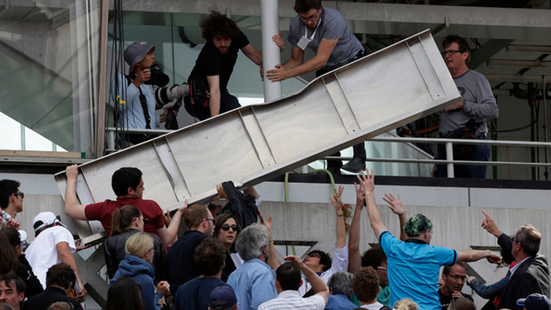 June 2, 2015: People remove a piece of metal which fell on a stand of center court as France's Jo-Wilfried Tsonga plays Japan's Kei Nishikori during their quarterfinal match of the French Open tennis tournament at the Roland Garros stadium in Paris, France.