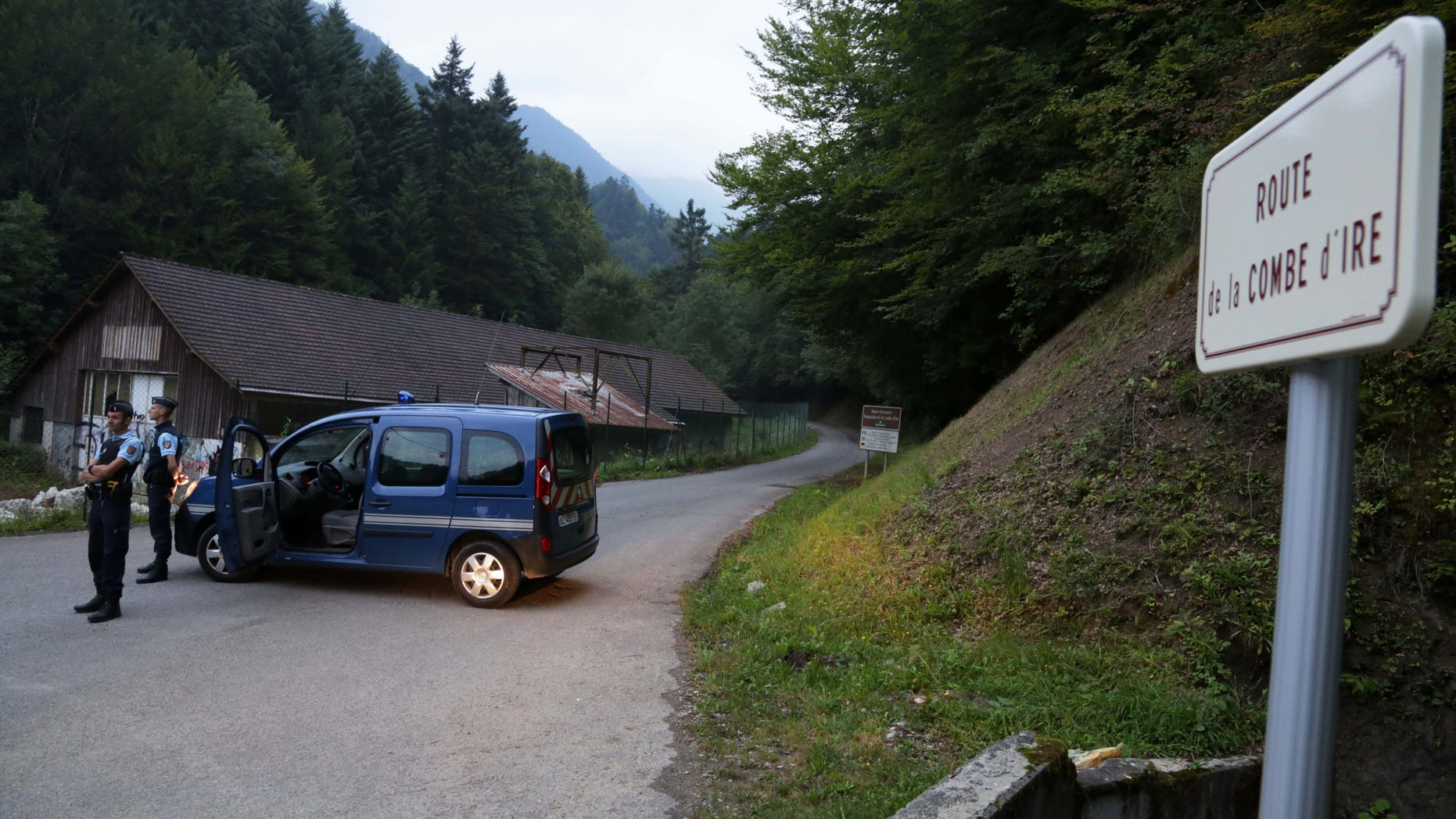 Sept. 5, 2012: Gendarmes block access to a killing site near Chevaline, French Alps.  French authorities say at least four people have been shot to death in a forest in the Alps.An official with the regional administration for the Haute-Savoie region says three of the bodies were found in a BMW registered in Britain.