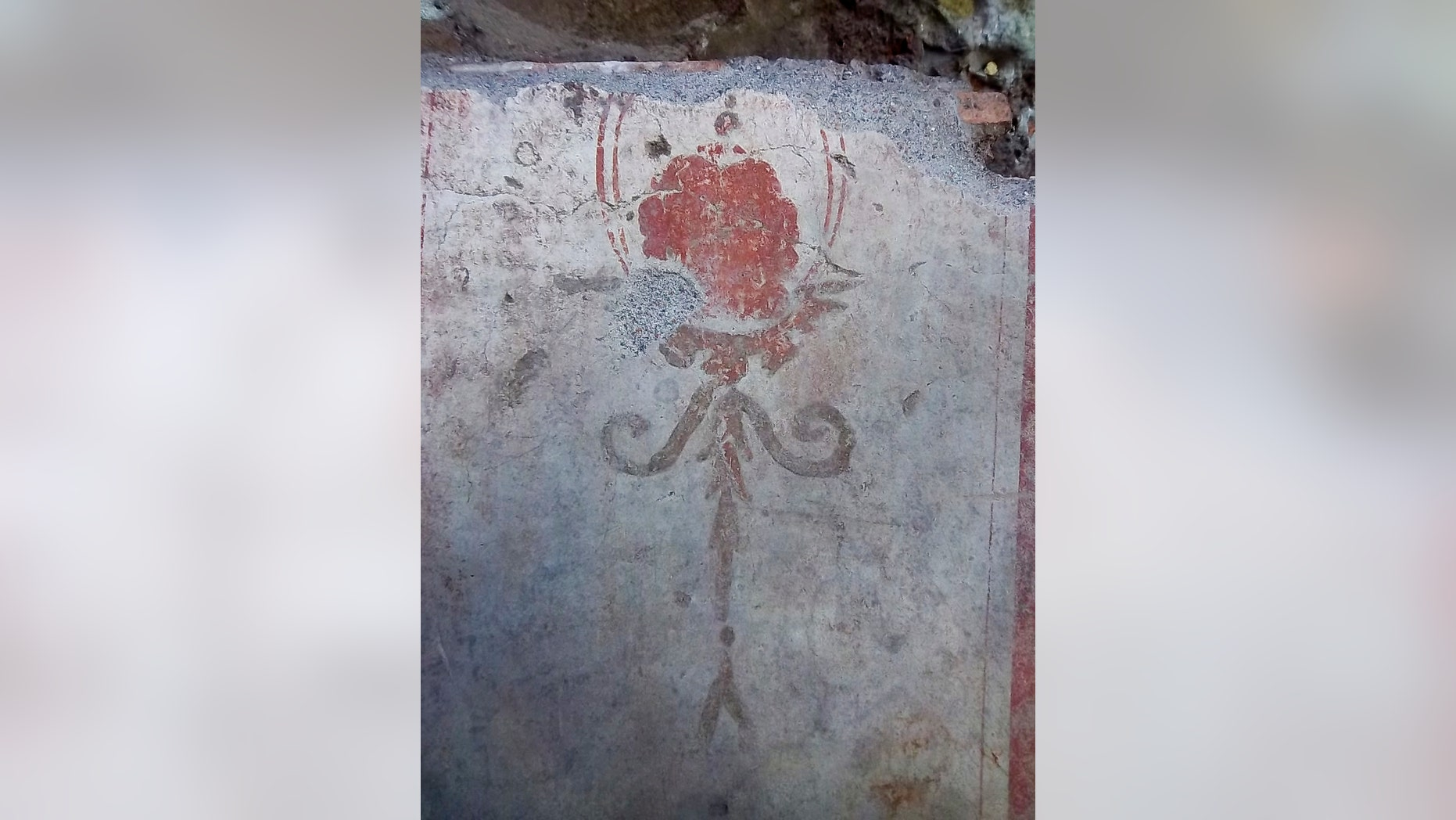 This photo made available Monday, June 26, 2017, by the Italian Culture Ministry, shows a frescoed wall segment, part of the charred ruins of a 3rd-century building that was unearthed while digging for Rome's new subway. The building was found on May 23 when examining the inside of a 10-meter (33-foot) deep hole bored into Rome near the ancient Aurelian Walls during construction work for the Metro C line. (Italian Culture Ministry Via AP)