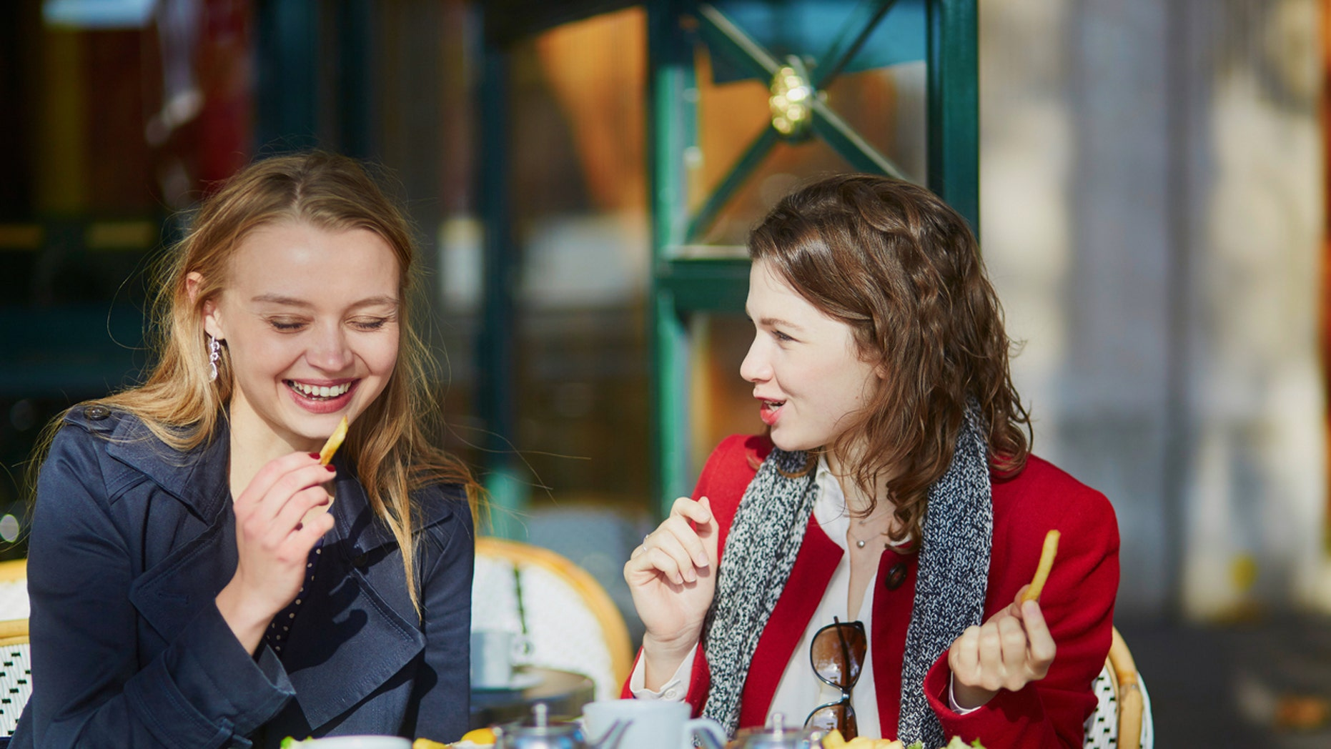 Two young girls in outdoor cafe, eating French fries.