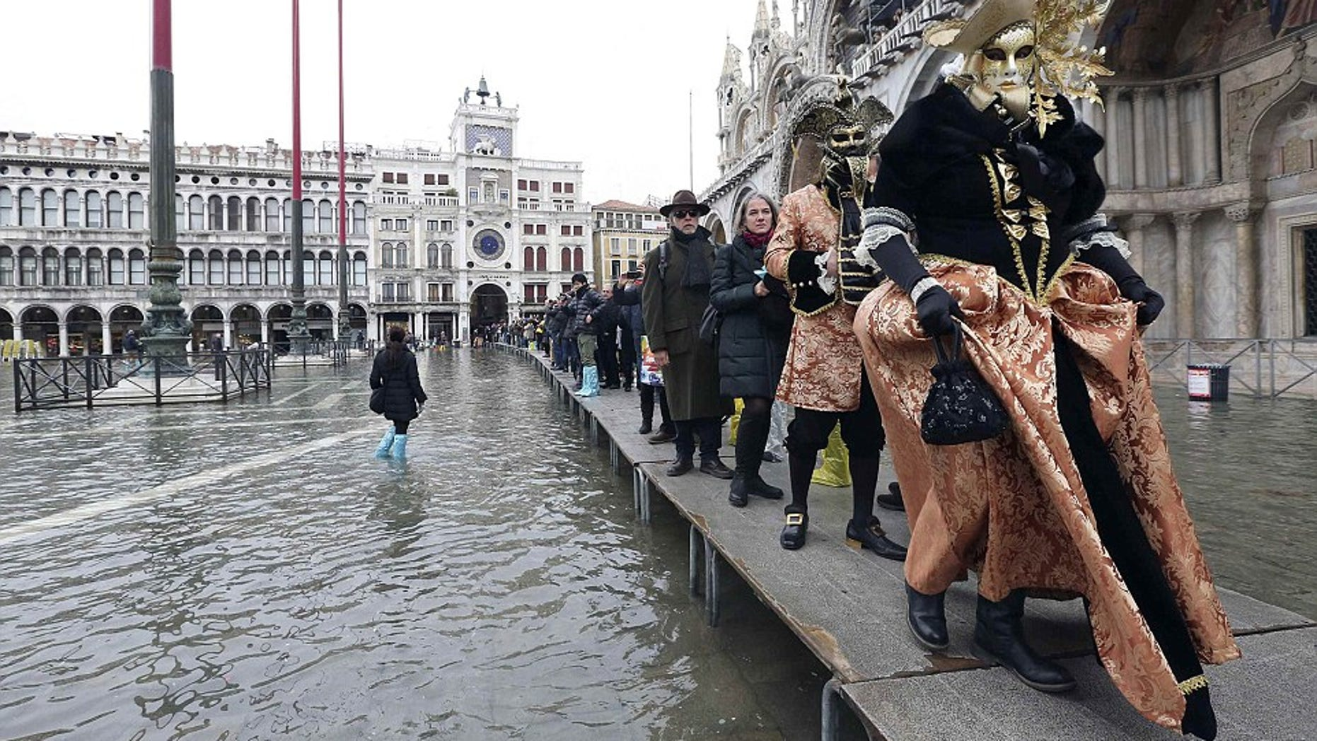 Tourists navigate Venice's city center on narrow wooden platforms.