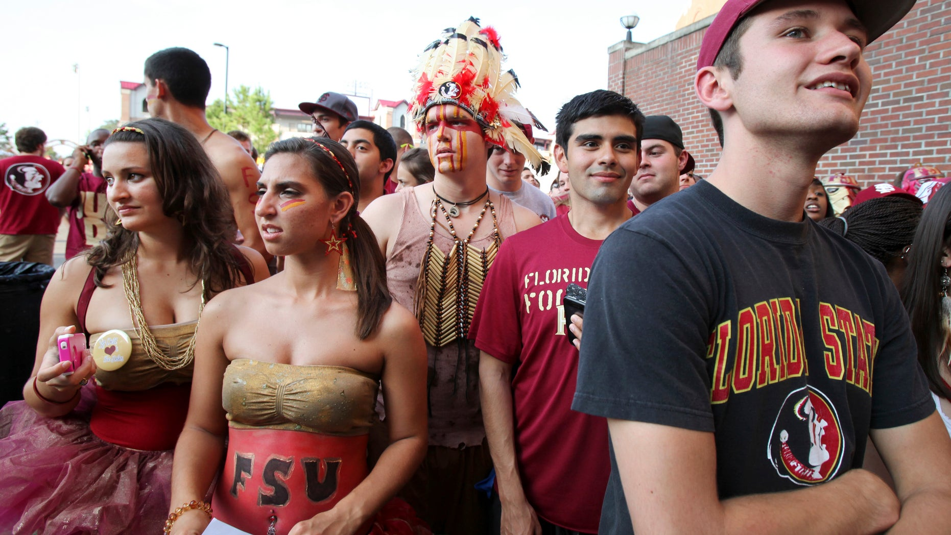 Will Faust (C) dons a headress while waiting to enter Doak Campbell Stadium with other Florida State University students before the start of NCAA football action against Oklahoma in Tallahassee, Florida, September 17, 2011. REUTERS/Daron Dean (UNITED STATES - Tags: SPORT FOOTBALL SOCIETY) - RTR2RGSC