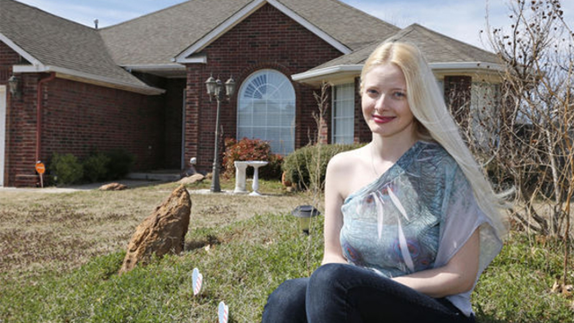 March 17, 2014: Jennifer Hunt poses for a photo outside her home in Noble, Okla. Hunt, whose husband was a soldier killed in the Fort Hood shooting, could get relief from a $6,000 tax bill under a measure Oklahoma legislators are considering that would grant some families benefits similar to those given after acts of terrorism.