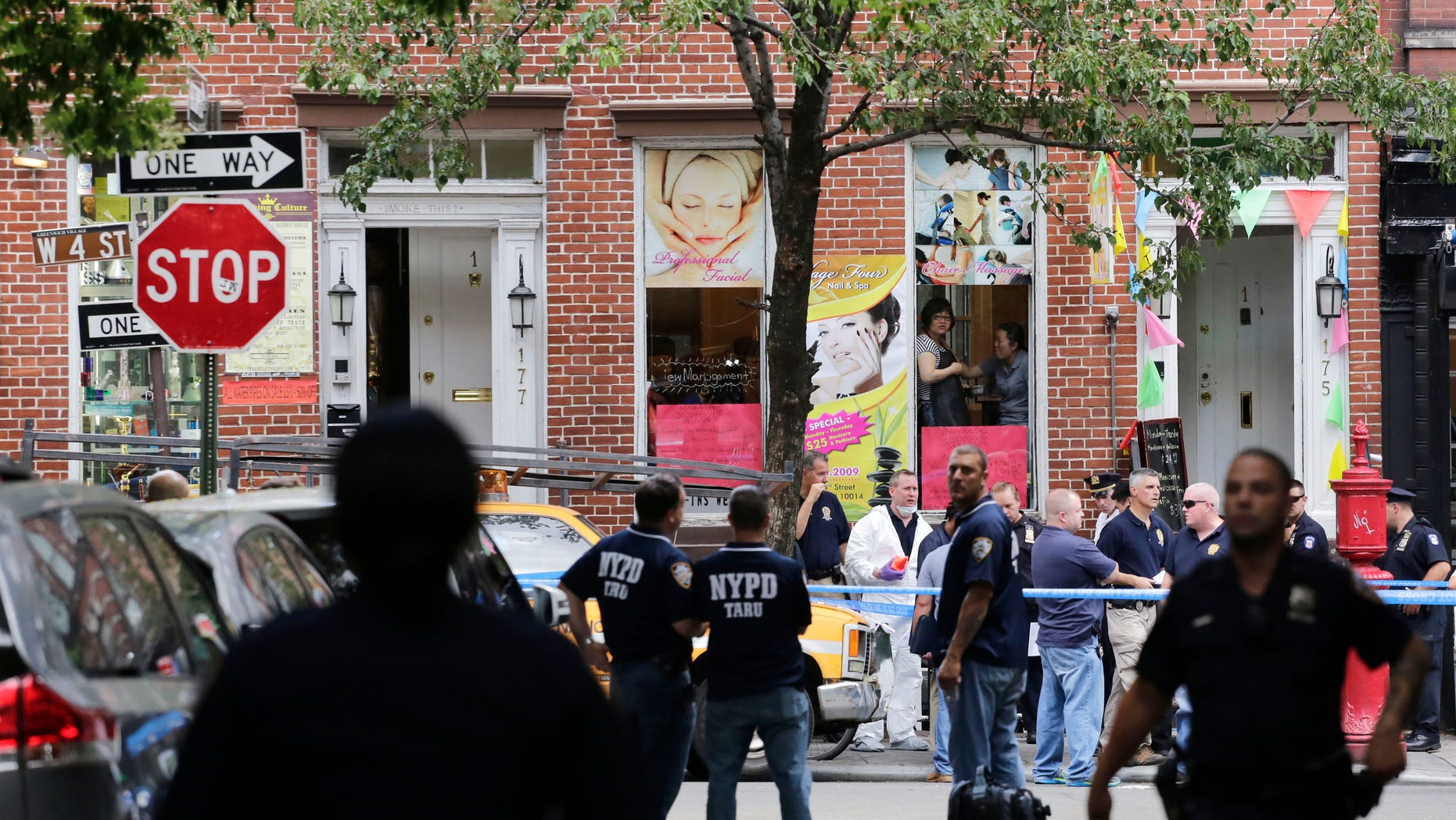 July 28, 2014: Police officers stand guard at the scene of a shooting in the Greenwich Village neighborhood in New York.