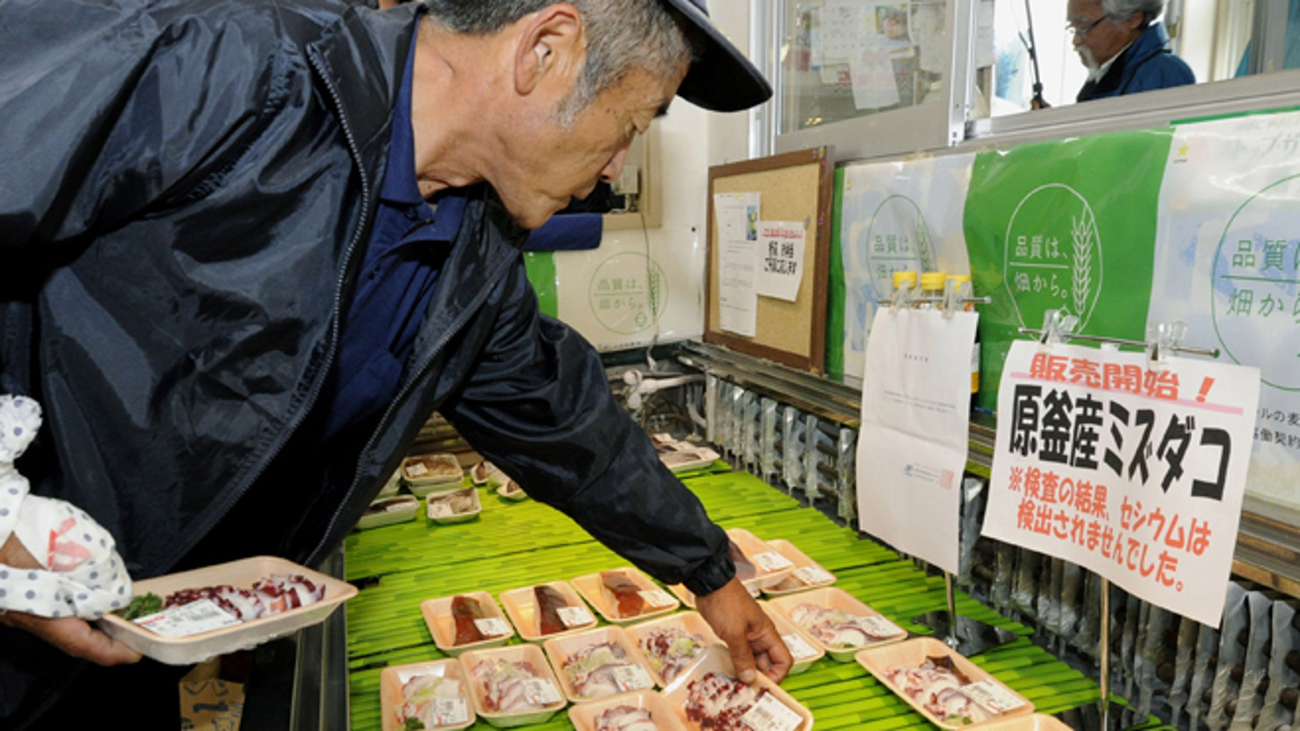 June 25: A shopper chooses packs of octopus caught in the water off Fukushima at a supermarket in Soma, Fukushima Prefecture, northeastern Japan.
